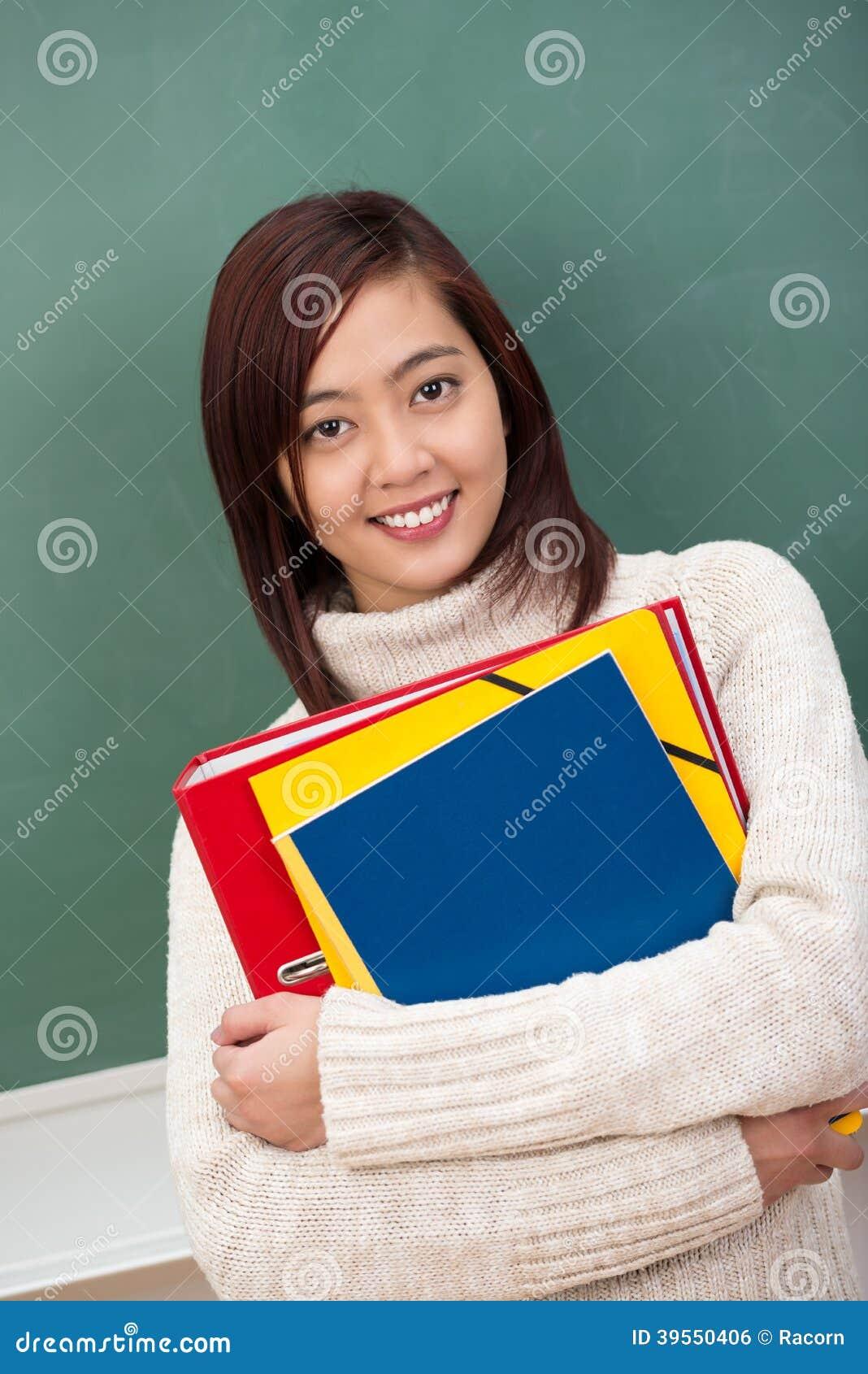 Nätt ung asiatisk student som knäpper fast mappar