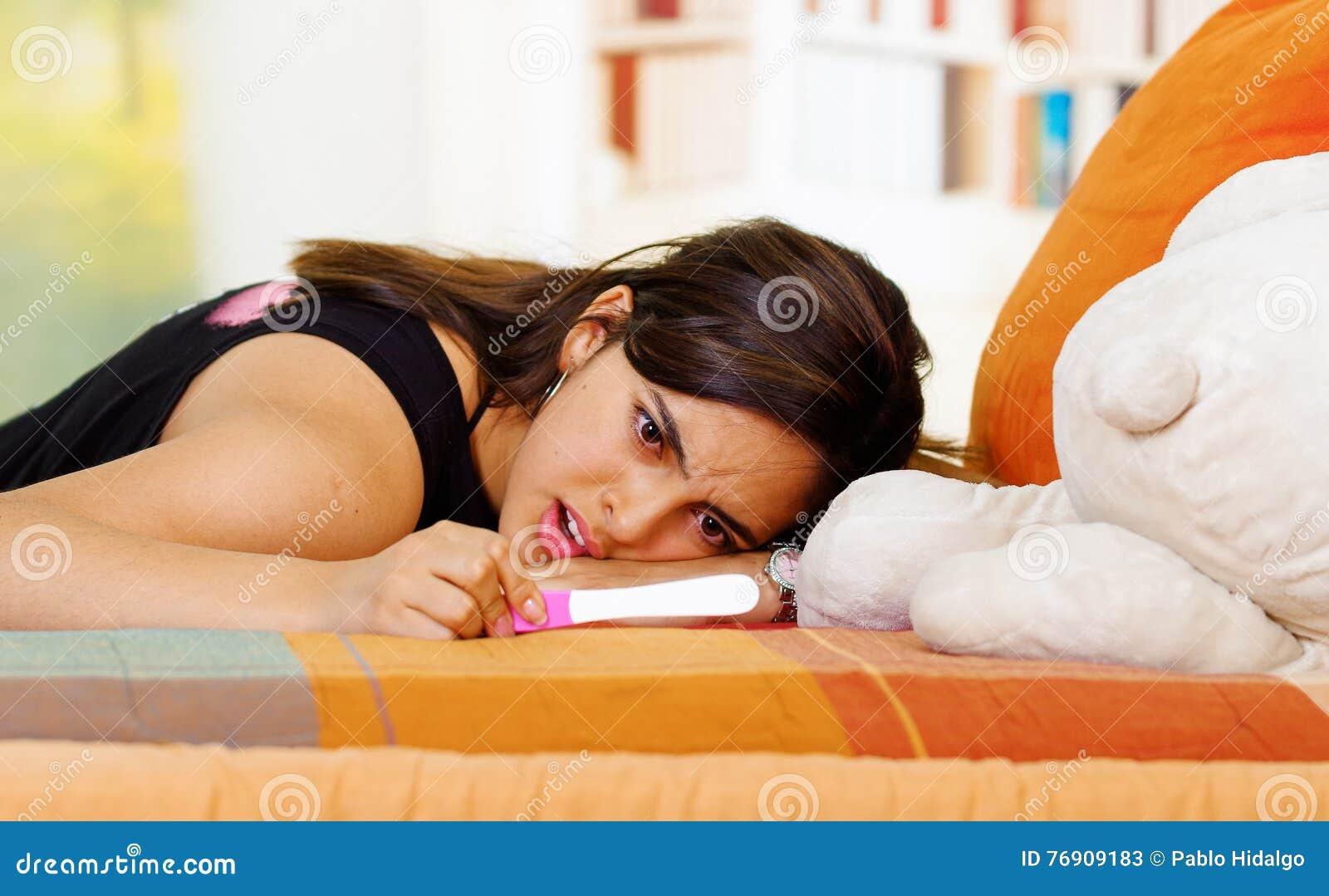Nätt ung brunettkvinna som ner ligger med det främsta havandeskaphemprovet, intensiv emotionell stirrande, trädgårds- fönster