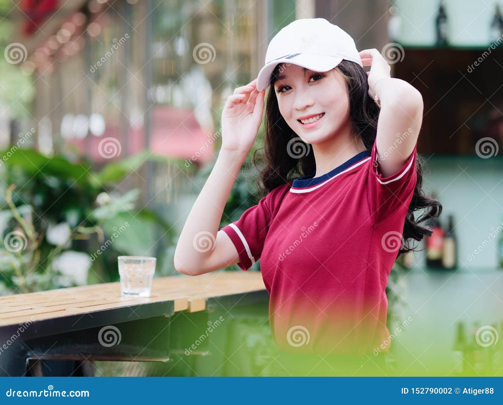 Nätt ung flicka för mode med svart långt hår, den bärande röda T-tröja och den vita baseballmössan som poserar utomhus- minimalis