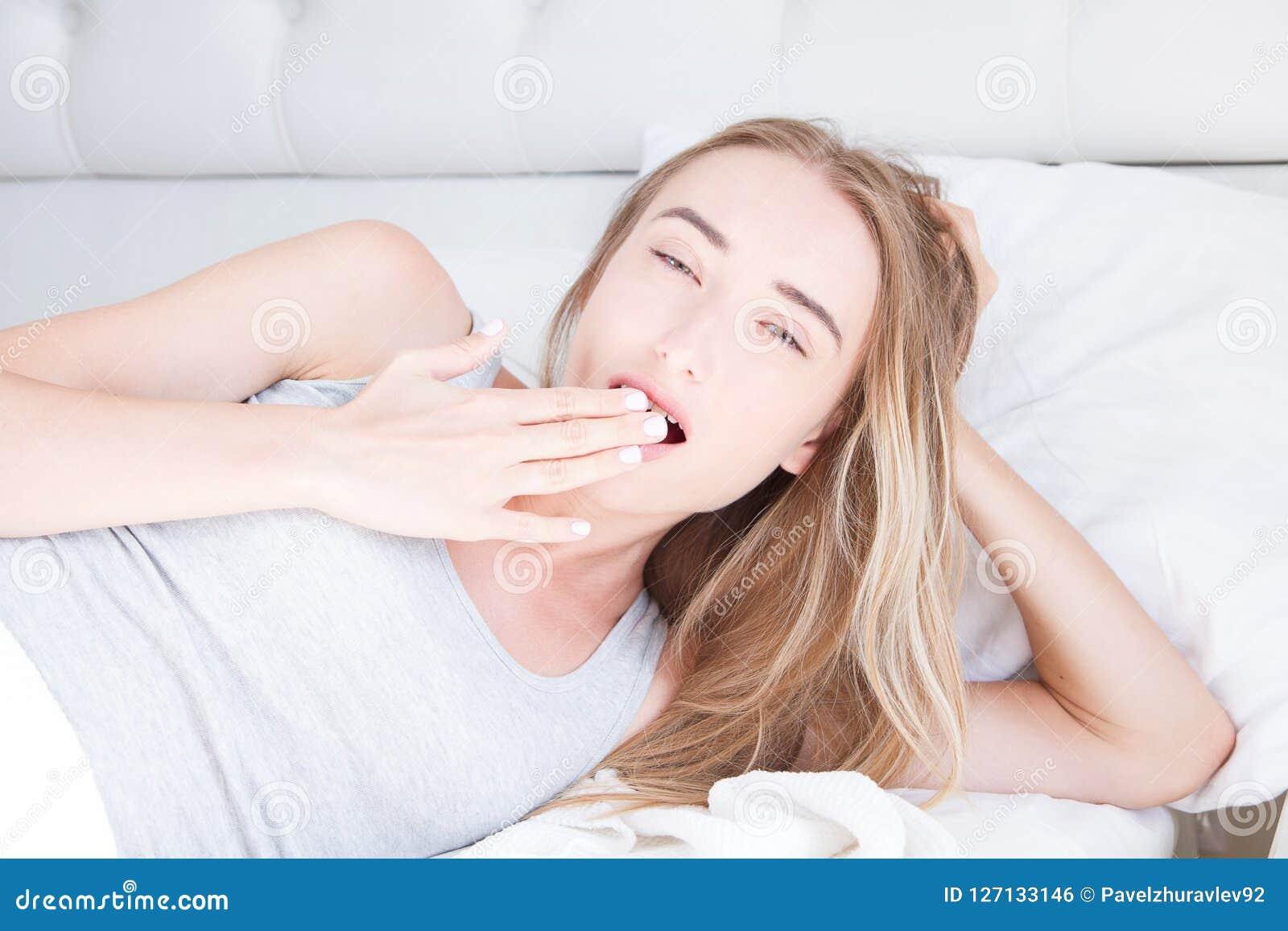 Nätt ung kvinna i säng, fritt utrymme Stående av den fundersamma härliga flickan som vaknar i morgon i hennes sovrum Godadröm
