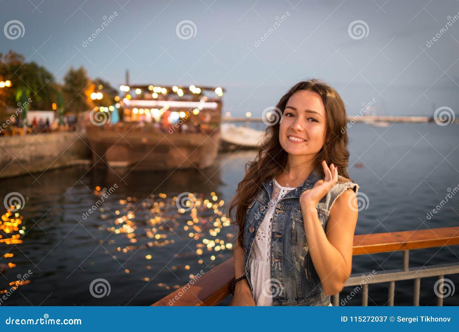 Nätt ung kvinna som går på stadspromenad nära havet i aftonen