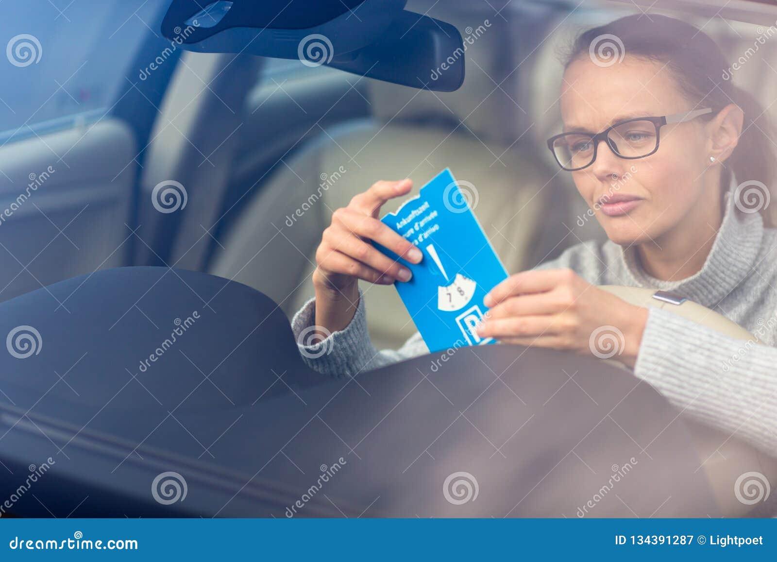 Nätt ung kvinna som kör hennes nya bil- sätta den nödvändiga parkera klockan bak vindrutan