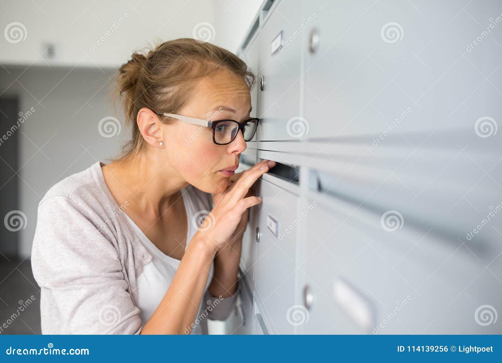 Nätt ung kvinna som kontrollerar hennes brevlåda