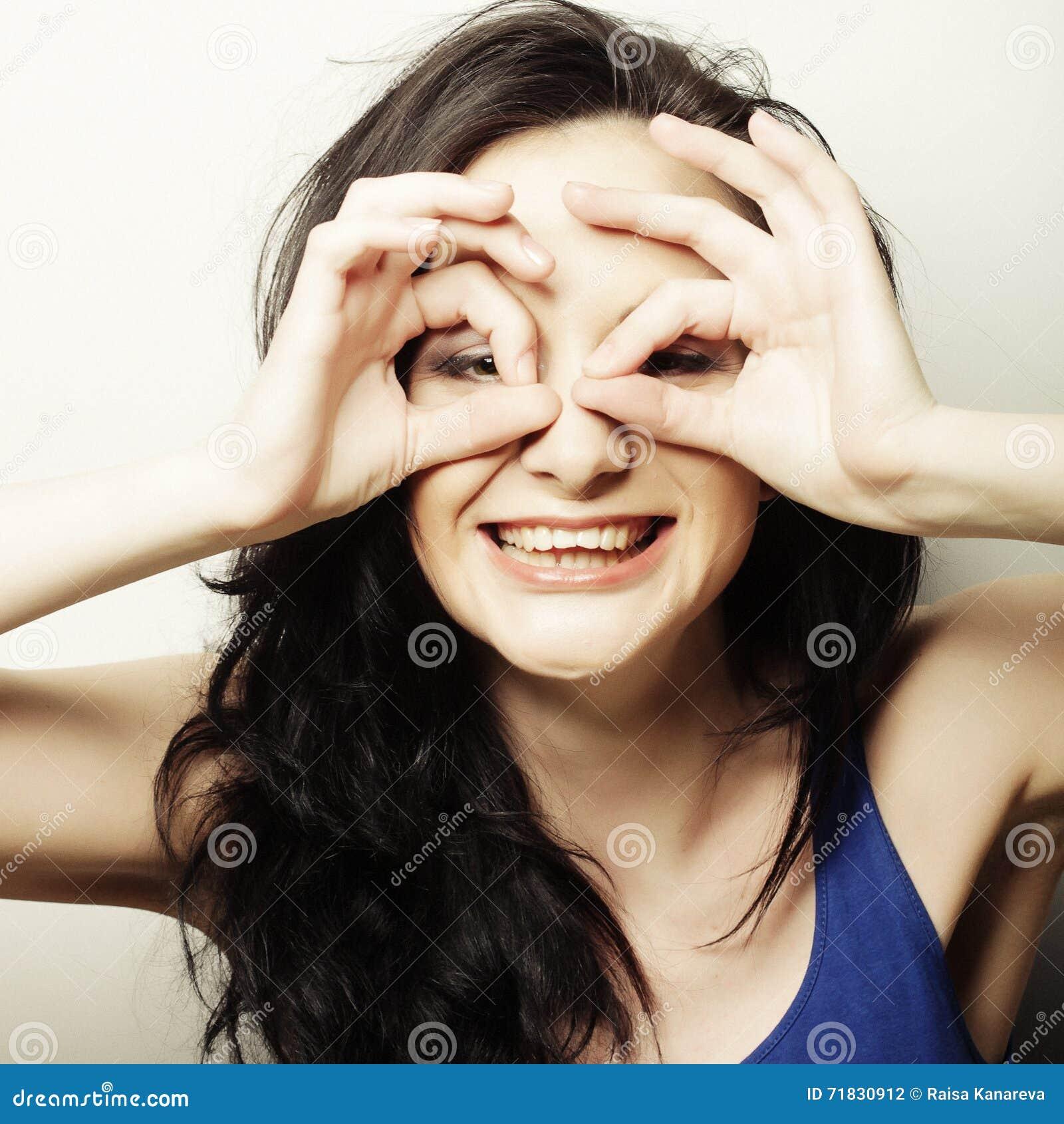 Nätt ung kvinna som söker efter något med öppna ögon för sned boll och
