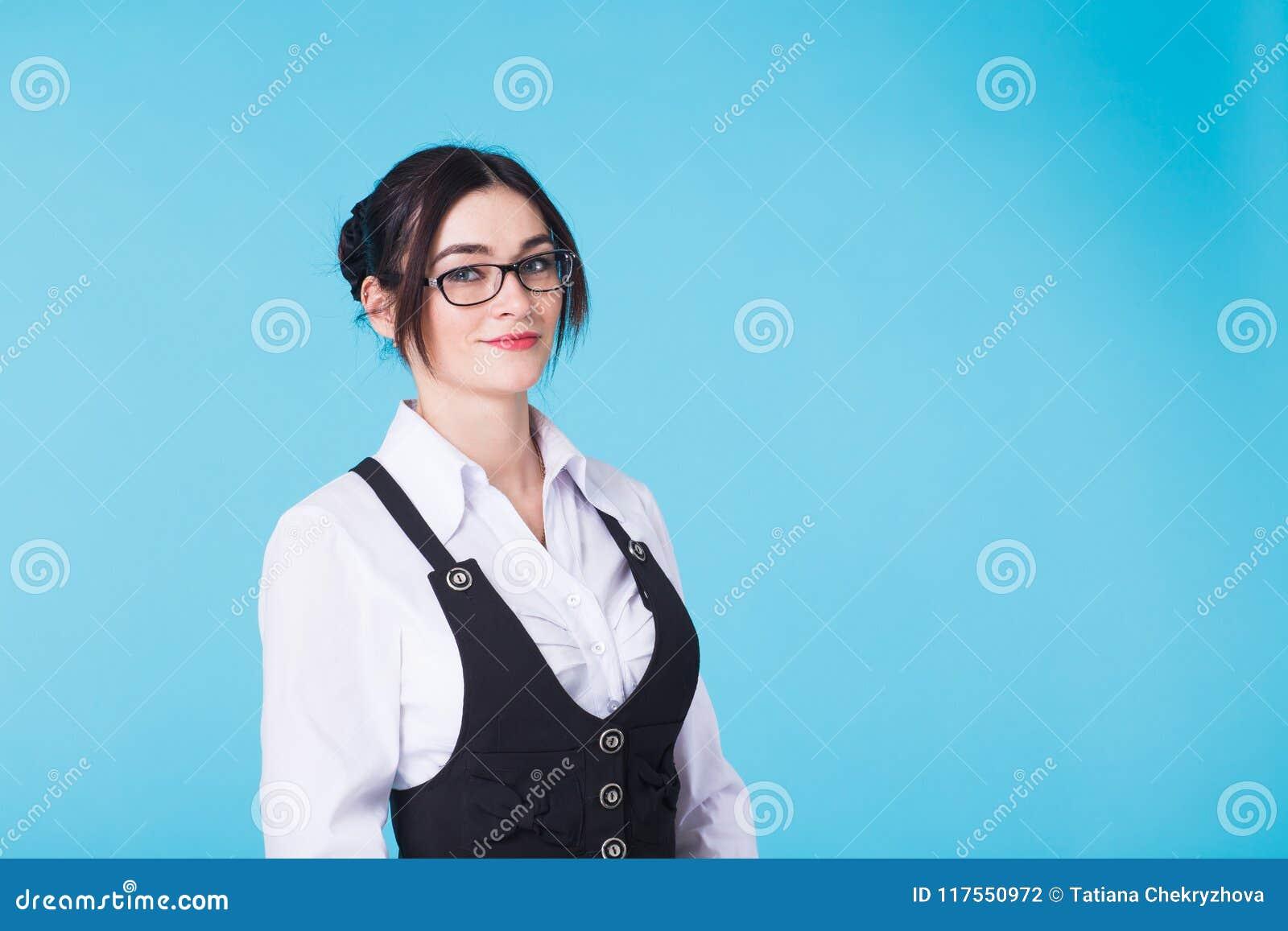 Nätt ung le brunettkvinna i exponeringsglas och waistcoaten som ser kameran på blå bakgrund