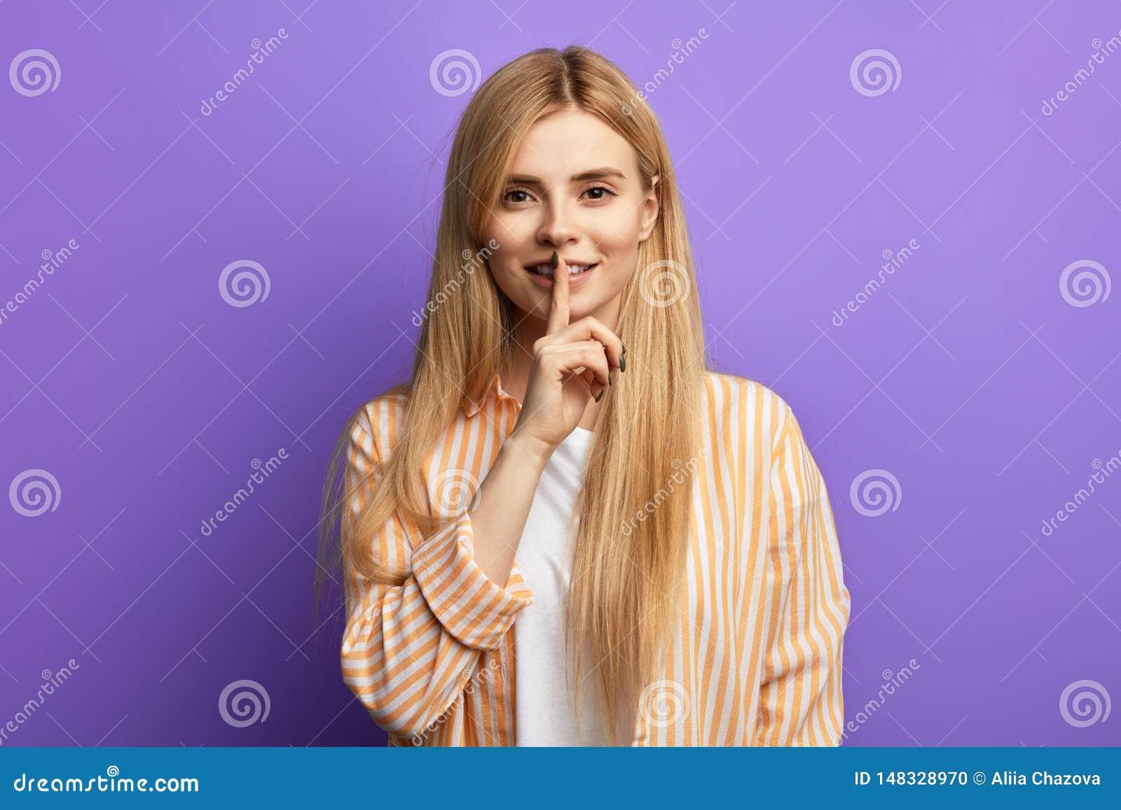 N?tt ung lycklig blond flicka som visar tystnadgest ?ver bl? bakgrund