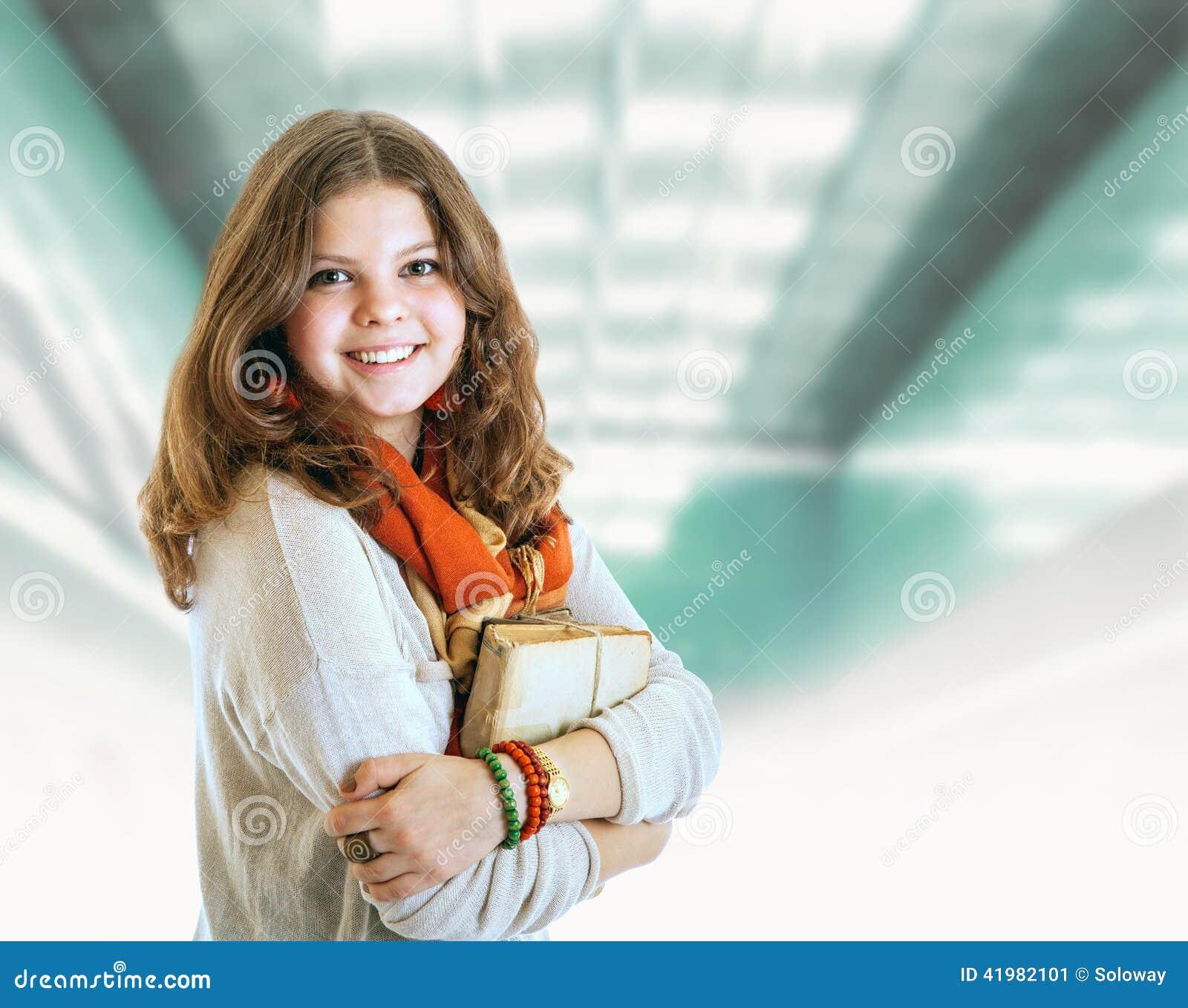 Nätt ung studentflickastående med böcker
