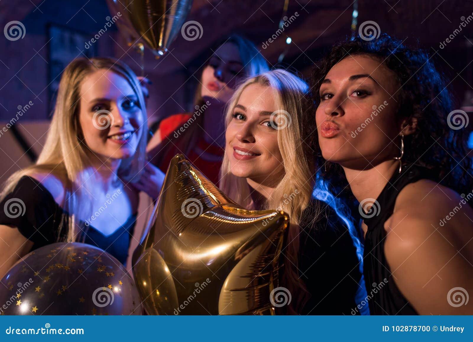 Nätta europeiska flickor som ler och att blåsa kyssar som har partiet på nattklubben