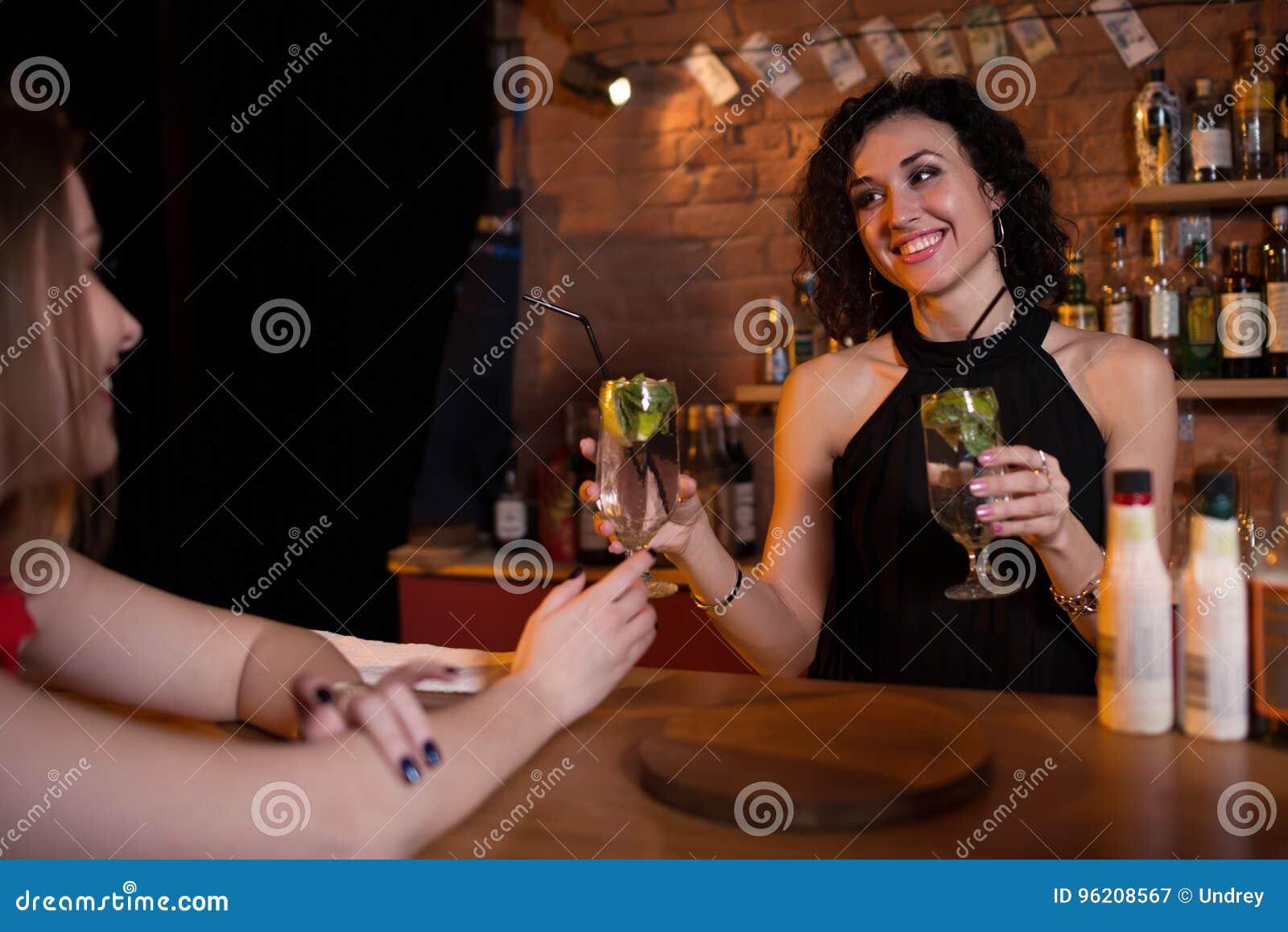 Nätta le erbjudande drinkar för kvinnlig bartender till gäster som står bak stångräknare