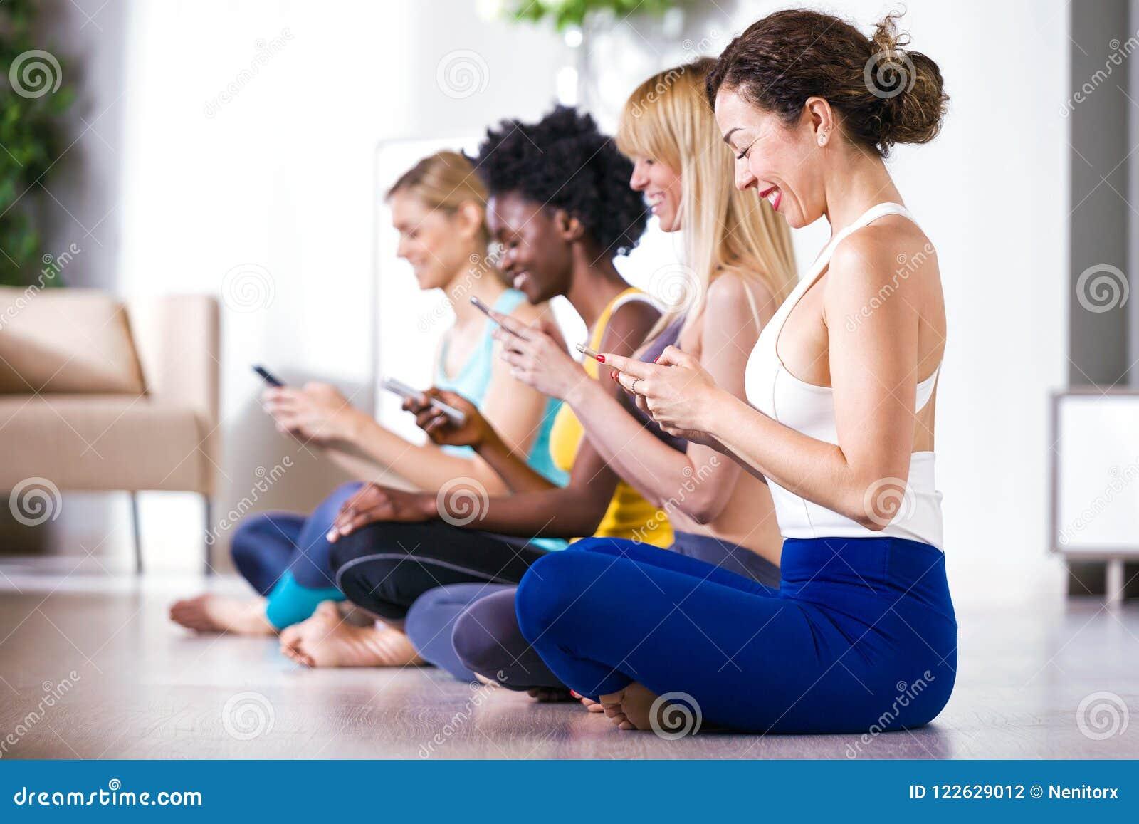 Nätta unga sportiga kvinnor som hemma använder mobiltelefonen efter yogaperiod