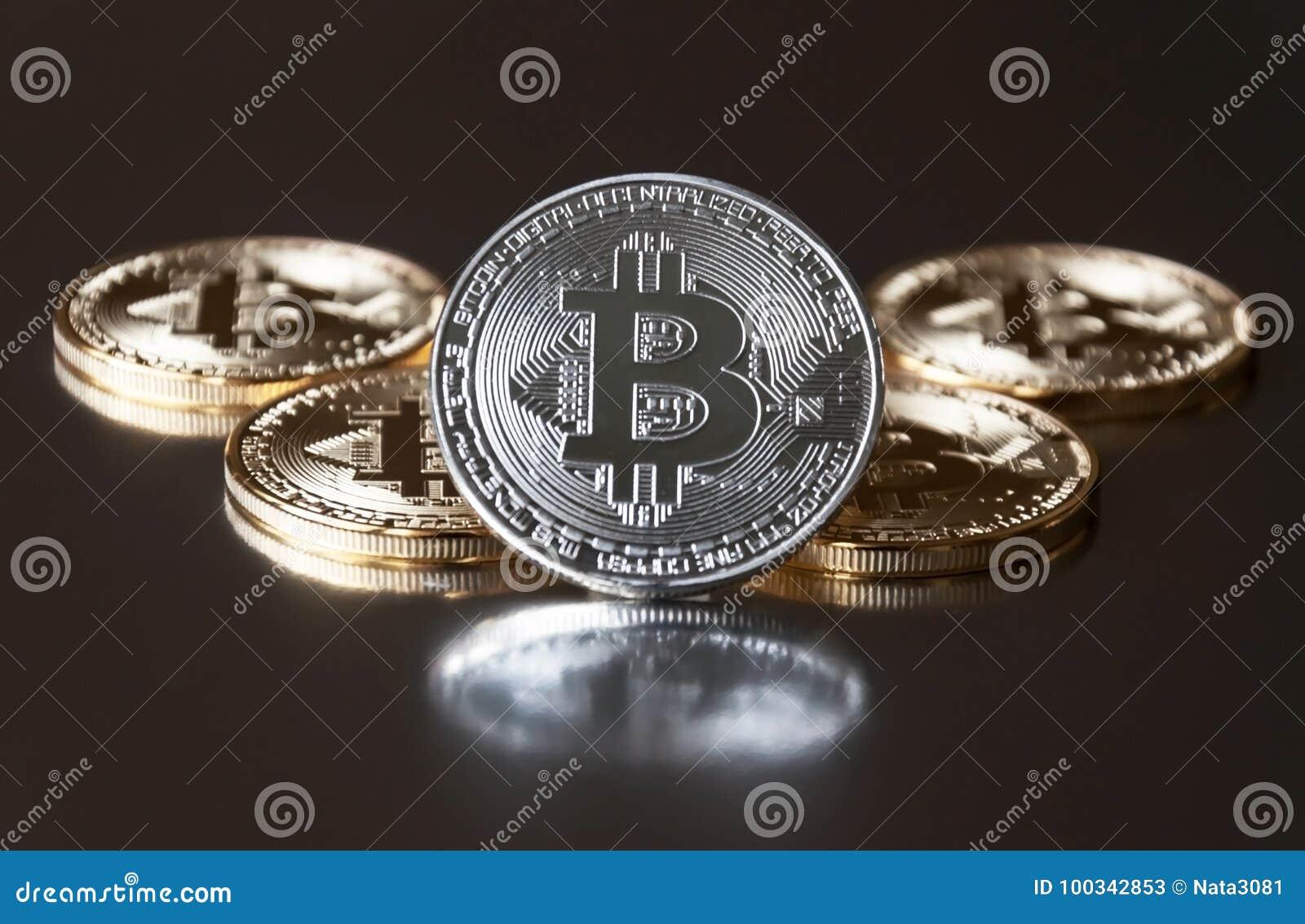 Några ligger blir guld- och silvermyntbitcoin eller på kanten på en mörk bakgrund Begreppet av crypto valuta
