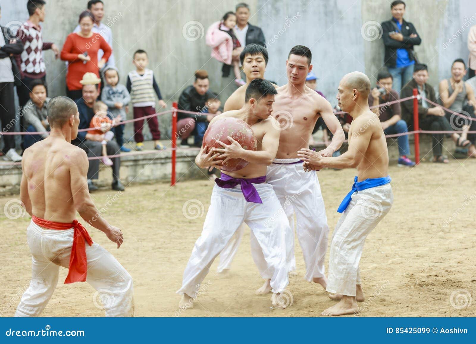 Några unga män spelar med den wood bollen i mån- nytt år för festival på Hanoi, Vietnam på Januari 27, 2016