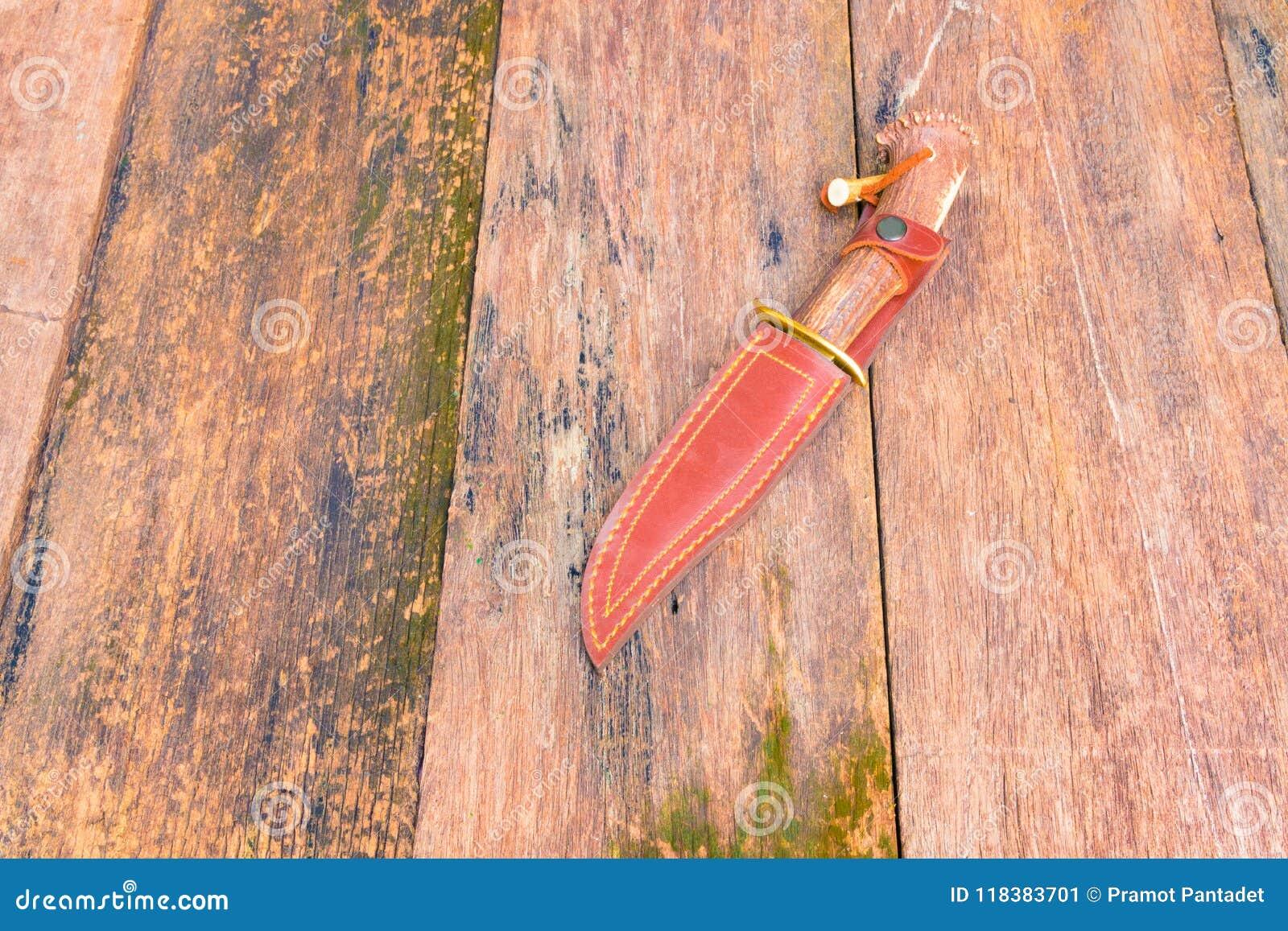 Nóż dla wycieczkować w sheath brązu skórze na drewnianym rocznika tle z kopii przestrzenią dodaje tekst
