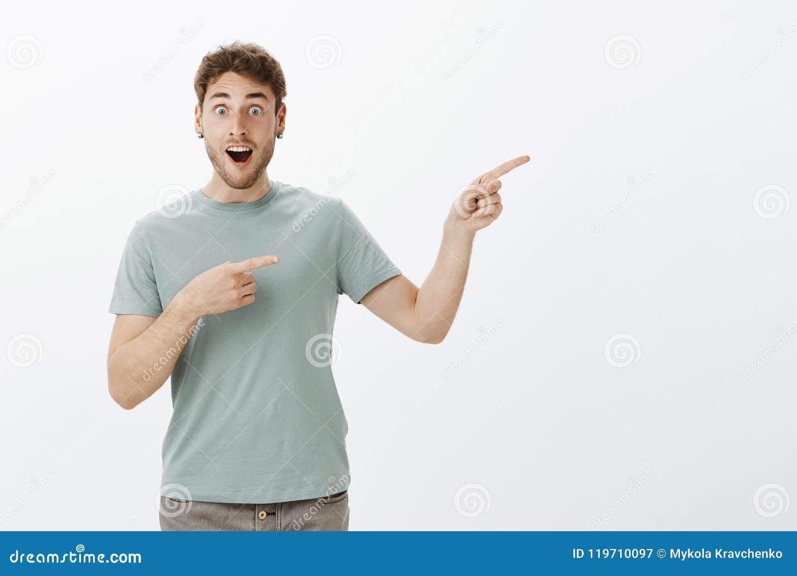 Nöjd förvånad attraktiv grabb med ganska hår som tappar käken, medan diskutera något förbluffa som rätt pekar med