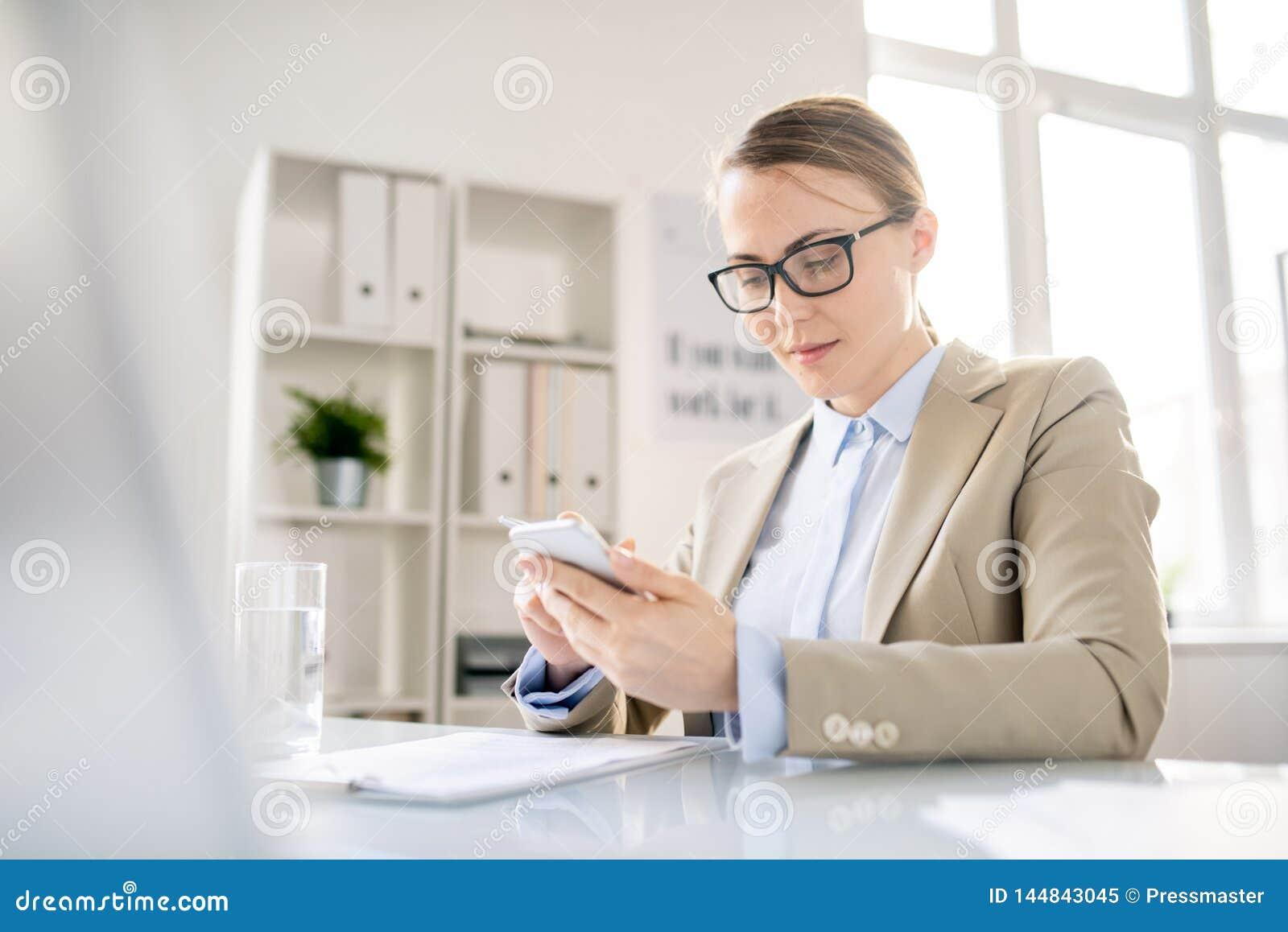 Nöjd kontorsanställd som använder grejen på arbetsplatsen