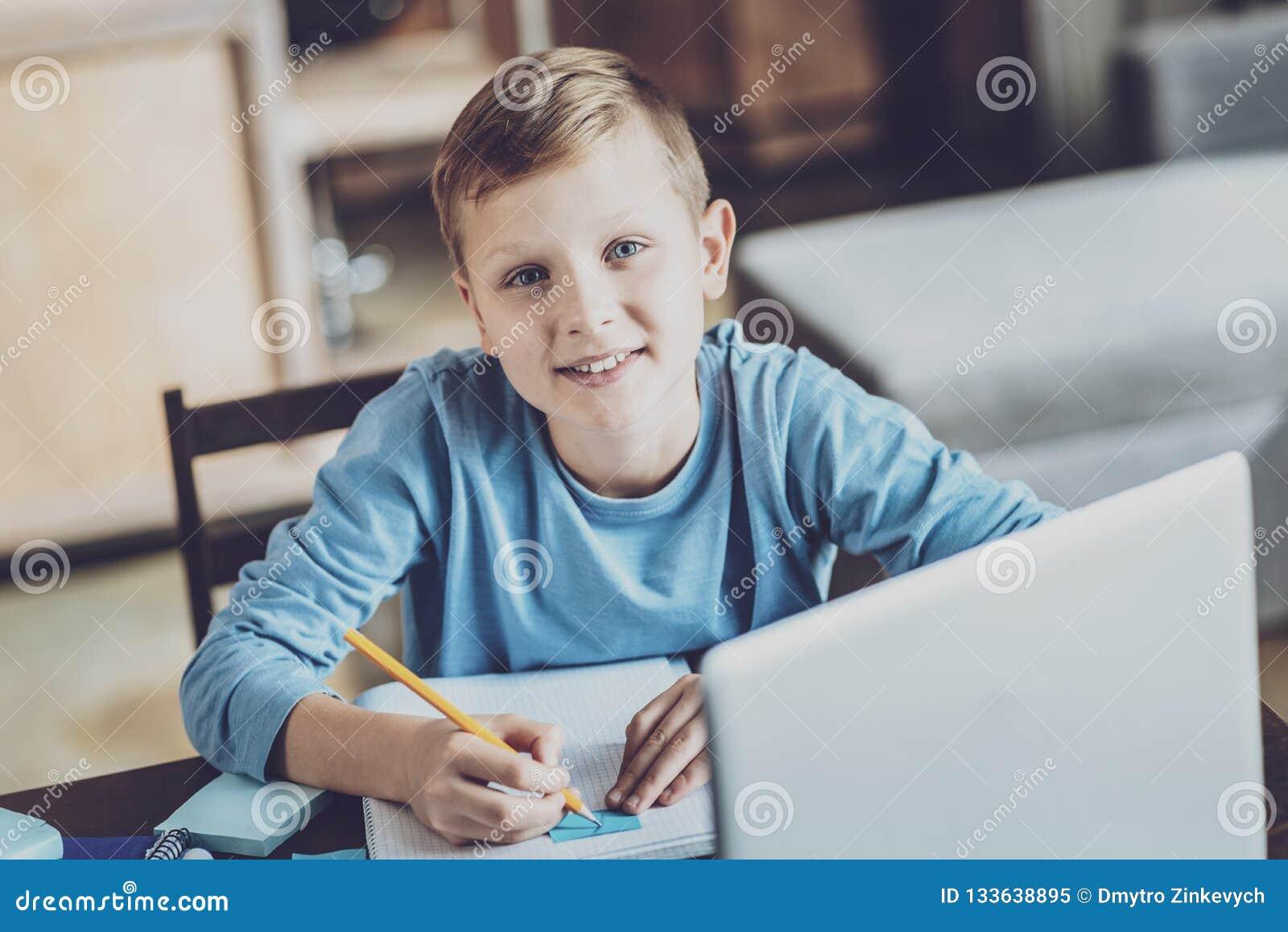 Nöjd unge som gör hem- uppgift med nöje