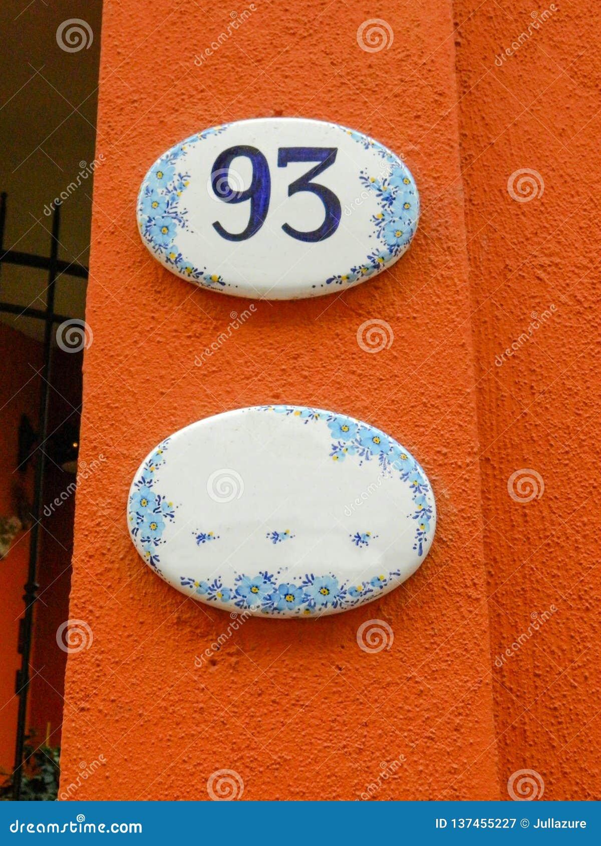 Número de casa, placa de cerámica con los dígitos azules, flores y el nombre de la calle Muestra decorativa del nombre o de númer