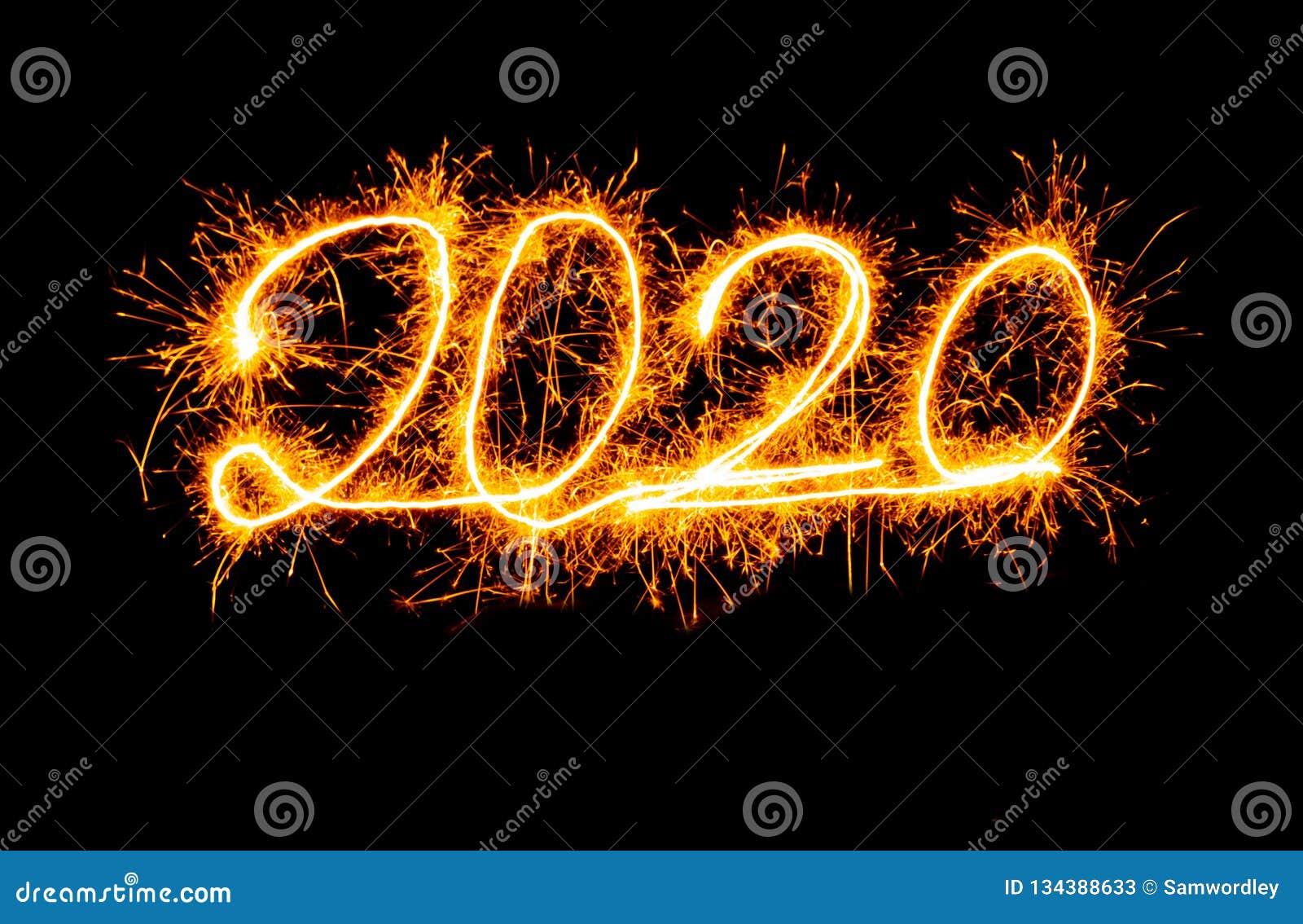Números dourados do ano novo feliz 2020 escritos com os fogos de artifício da faísca isolados no fundo preto