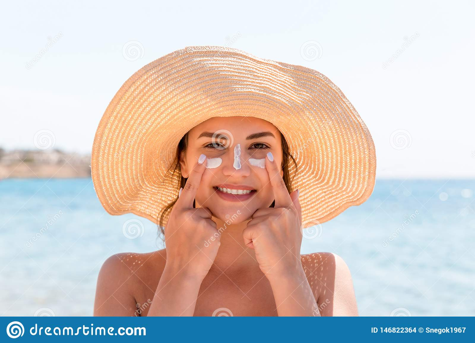 N?r du ler kvinnan i hatt applicerar sunscreen p? hennes framsida indisk stil