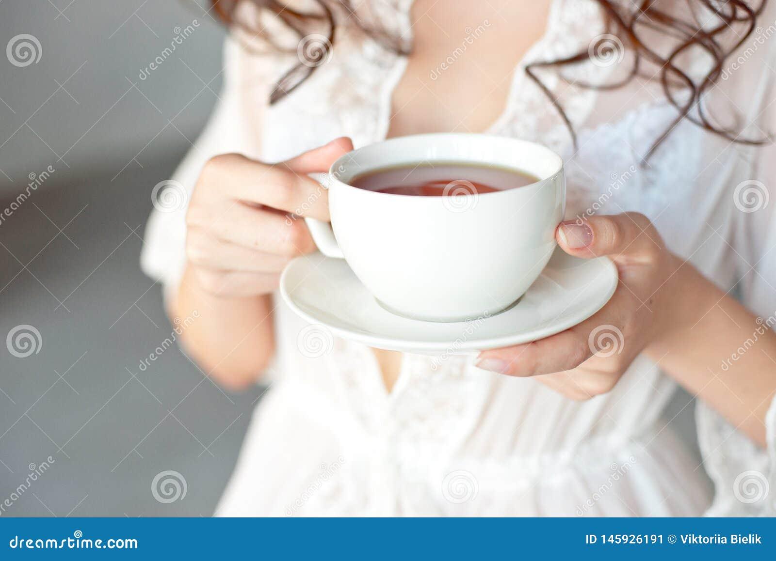 N?rbild av en vit kopp av varmt lattekonstkaffe med en hj?rtaform i h?nderna av en ung flicka