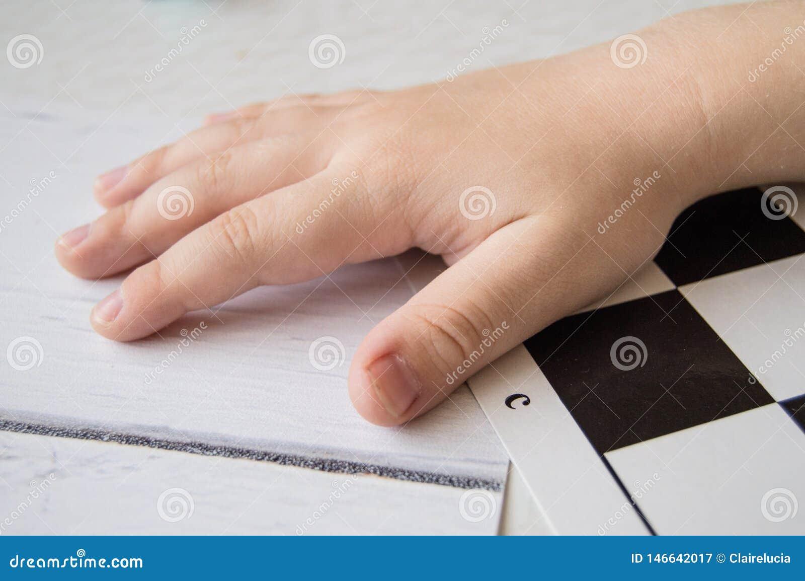 N?rbild av ett sm?barns hand som ligger p? schackbr?det, begreppet av att l?ra och intellektuell utveckling av barn
