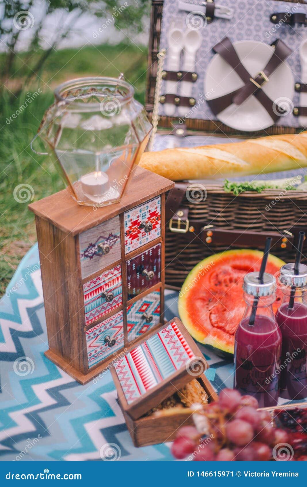 N?rbildpicknick i natur En stearinljus i en ljusstake står på en liten skänk, bredvid den ligger mat - vattenmelon, druvakex,