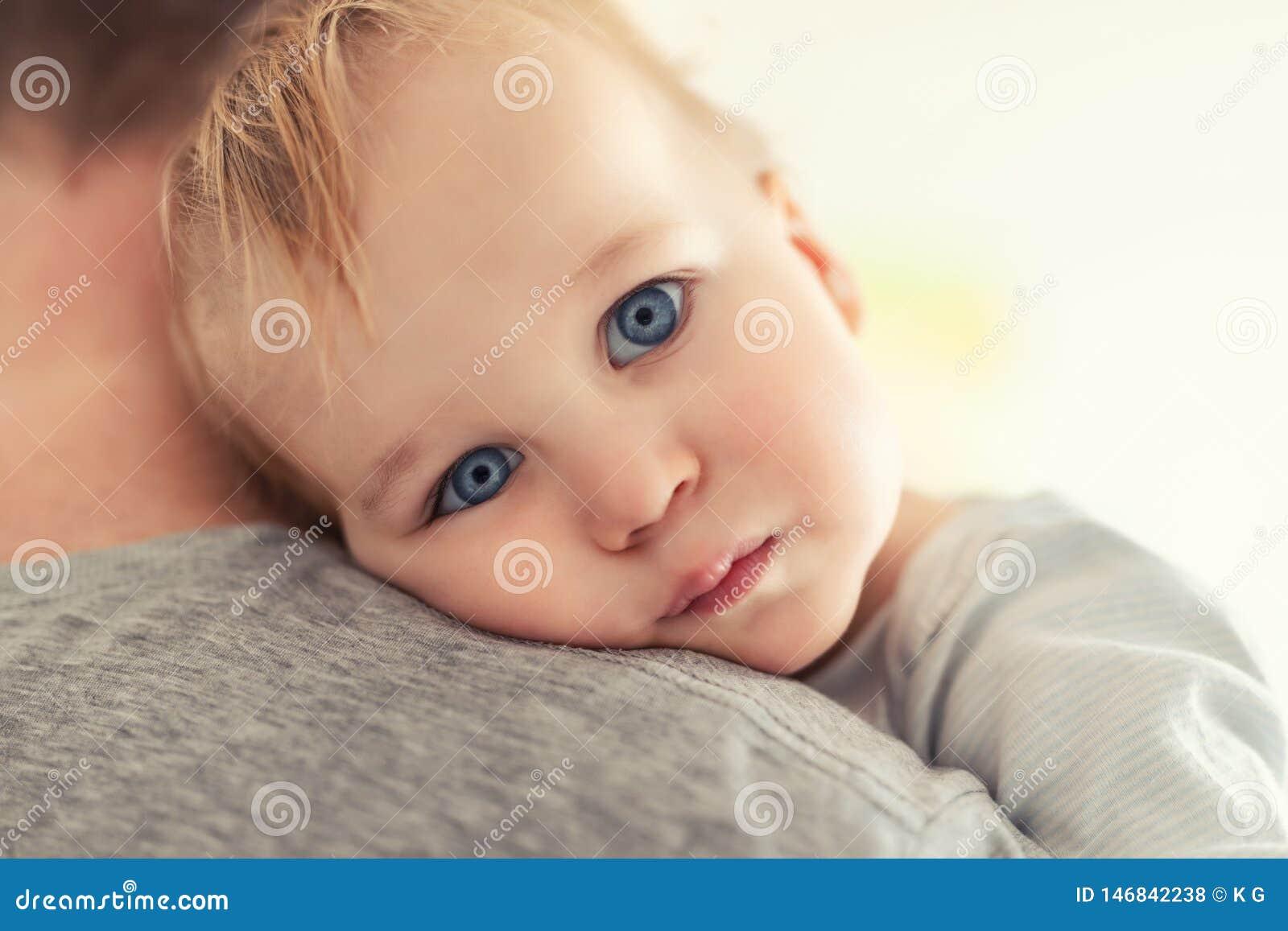 N?rbildst?enden av den gulliga f?rtjusande blonda caucasian litet barnpojken p? f?der knuffar inomhus S?t k?nslas?kerhet f?r lite