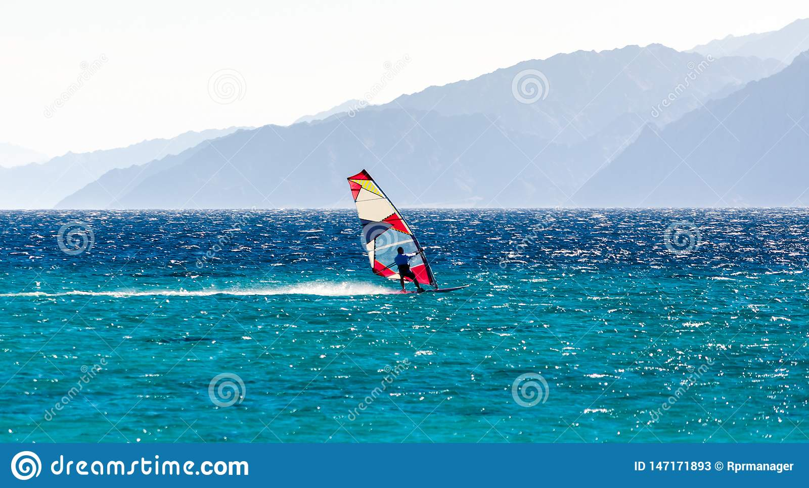 ??n surferritten in het Rode Overzees tegen de achtergrond van een rotsachtige kust in Egypte