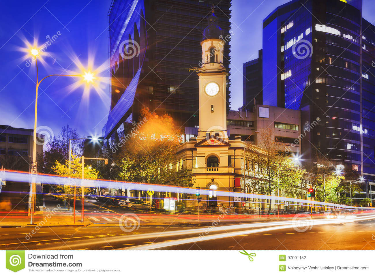 Historic heritage North Sydney post office building with clock tower  against tall modern business high-rises at sunset on car traffic street. adc8b11aeccb9