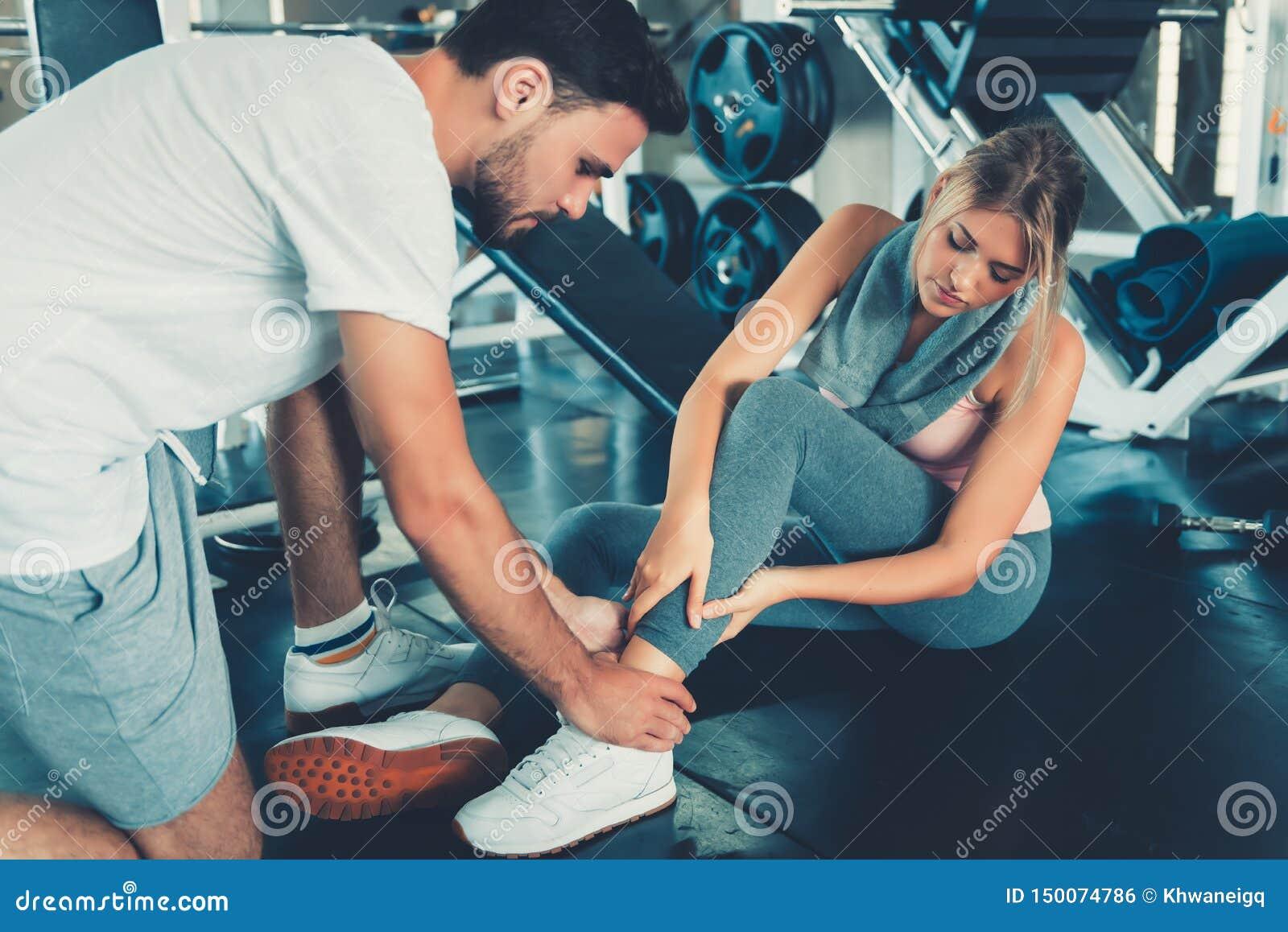 N?tt kvinna som har skada under ?vning i idrottshall medan hennes par som tar f?rsta hj?lpen-, olycks- och sportkonditionbegrepp