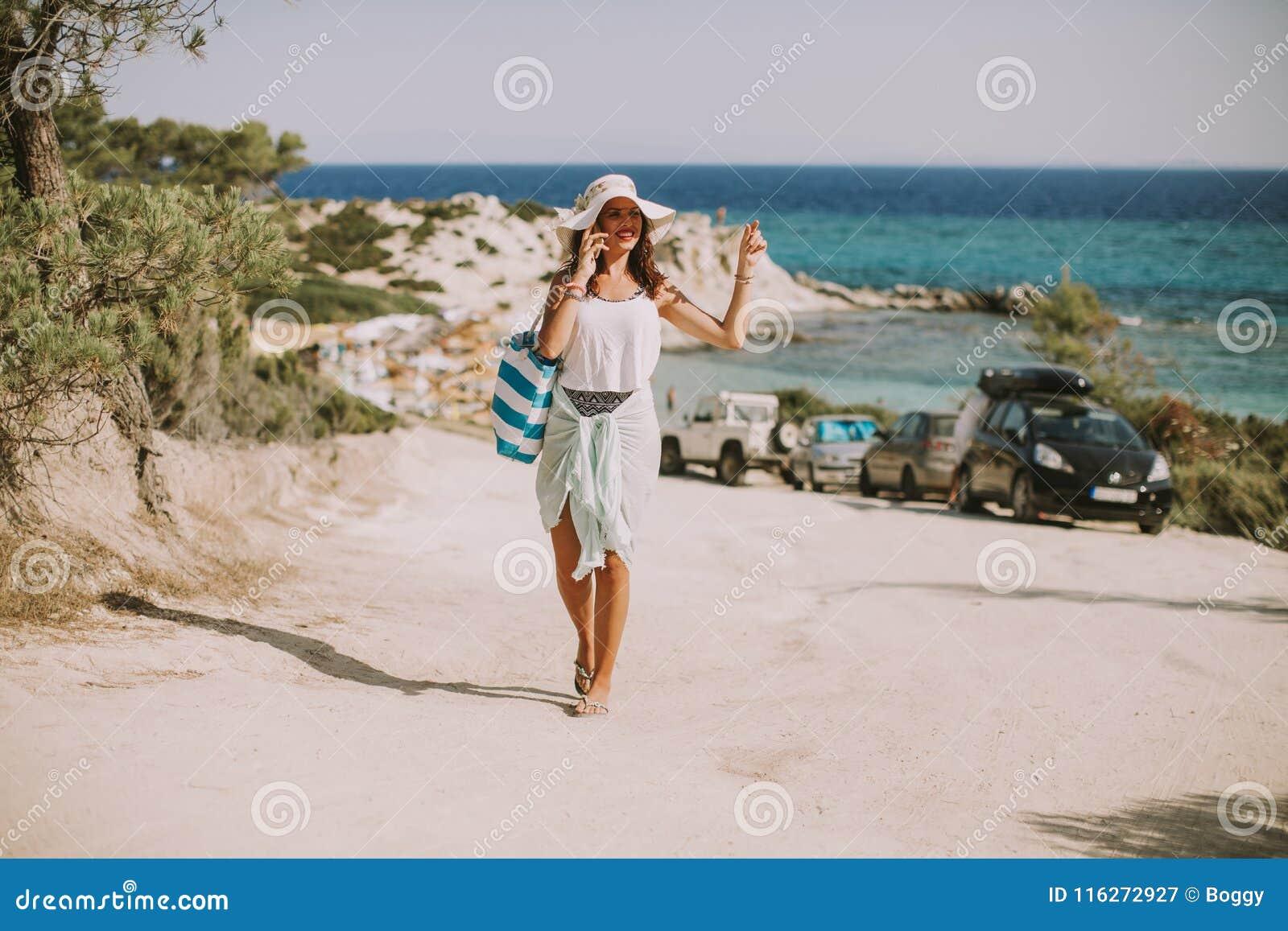 N?tt ung kvinna med en p?se genom att anv?nda mobiltelefonen p? stranden