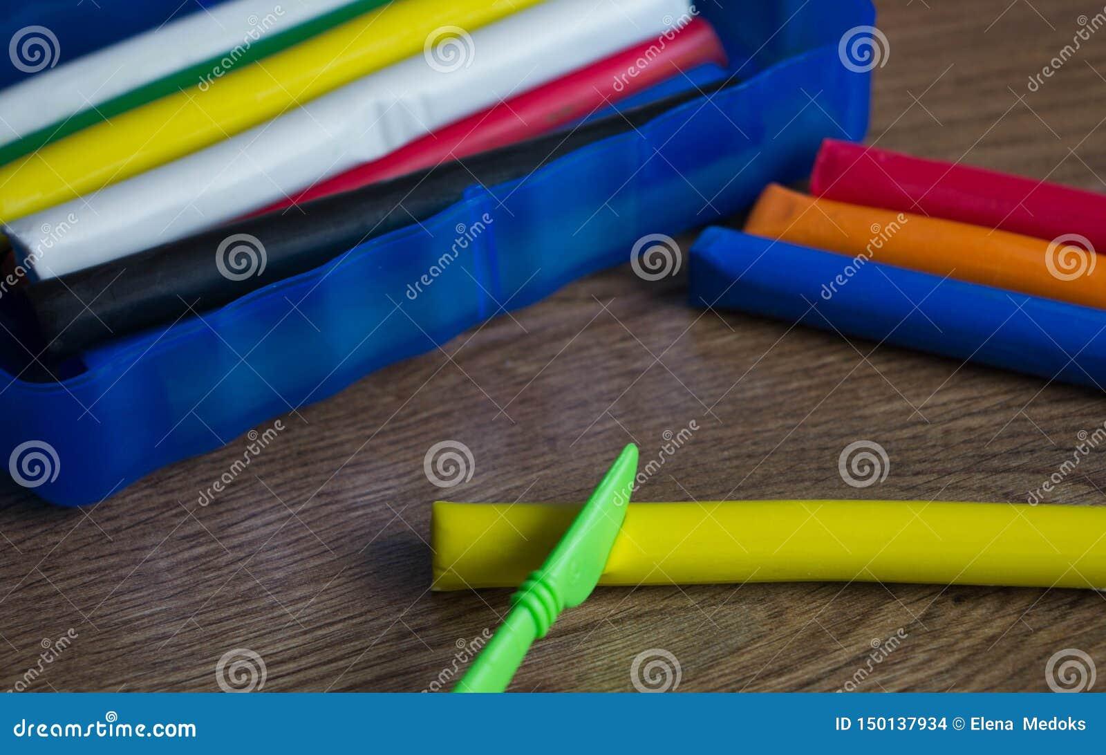 Na drewnianym stole tam jest błękitny pudełko z różnymi kawałkami plastelina, obok go jest barwiący plastelina i plasti
