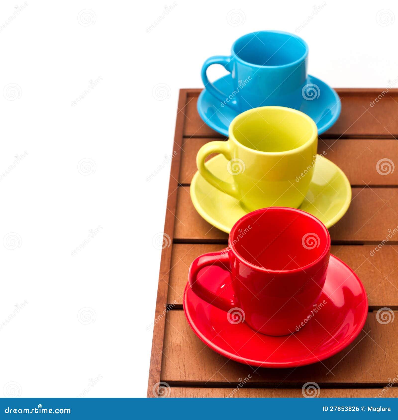 Na drewnianym tabletop kolorowe filiżanki
