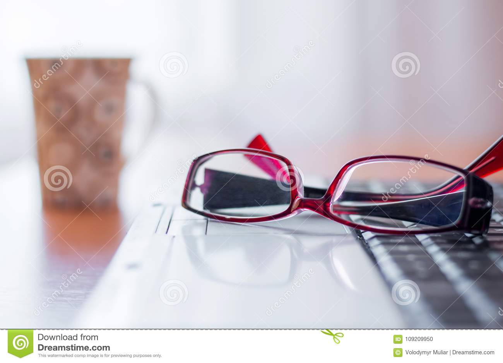 Na laptopu kłamstwa szkłach, dalszy na stole jest filiżanka w,