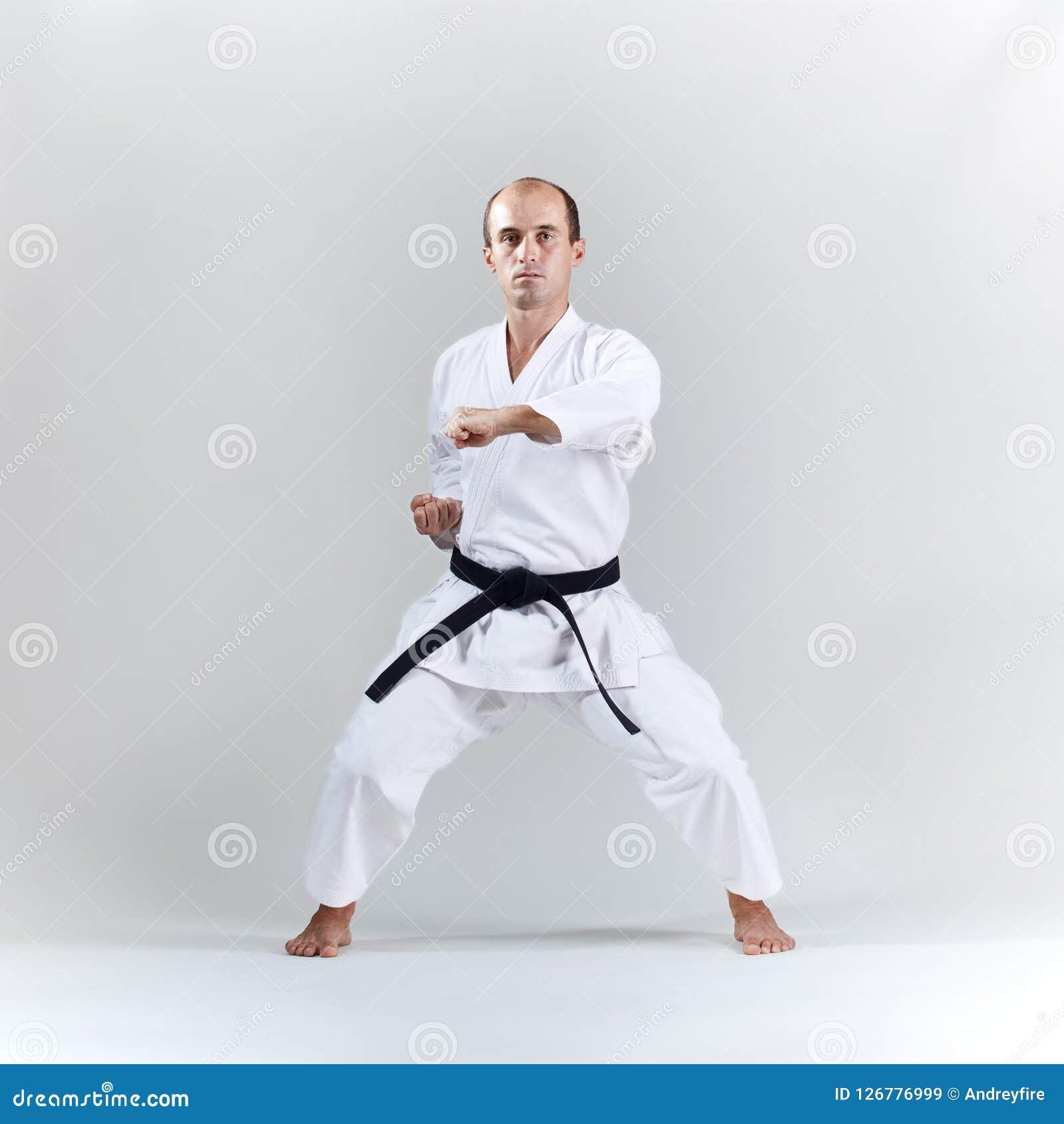 Na lekkim tle, dorosły sportowiec trenuje formalnego karate ćwiczenie w białym karategi