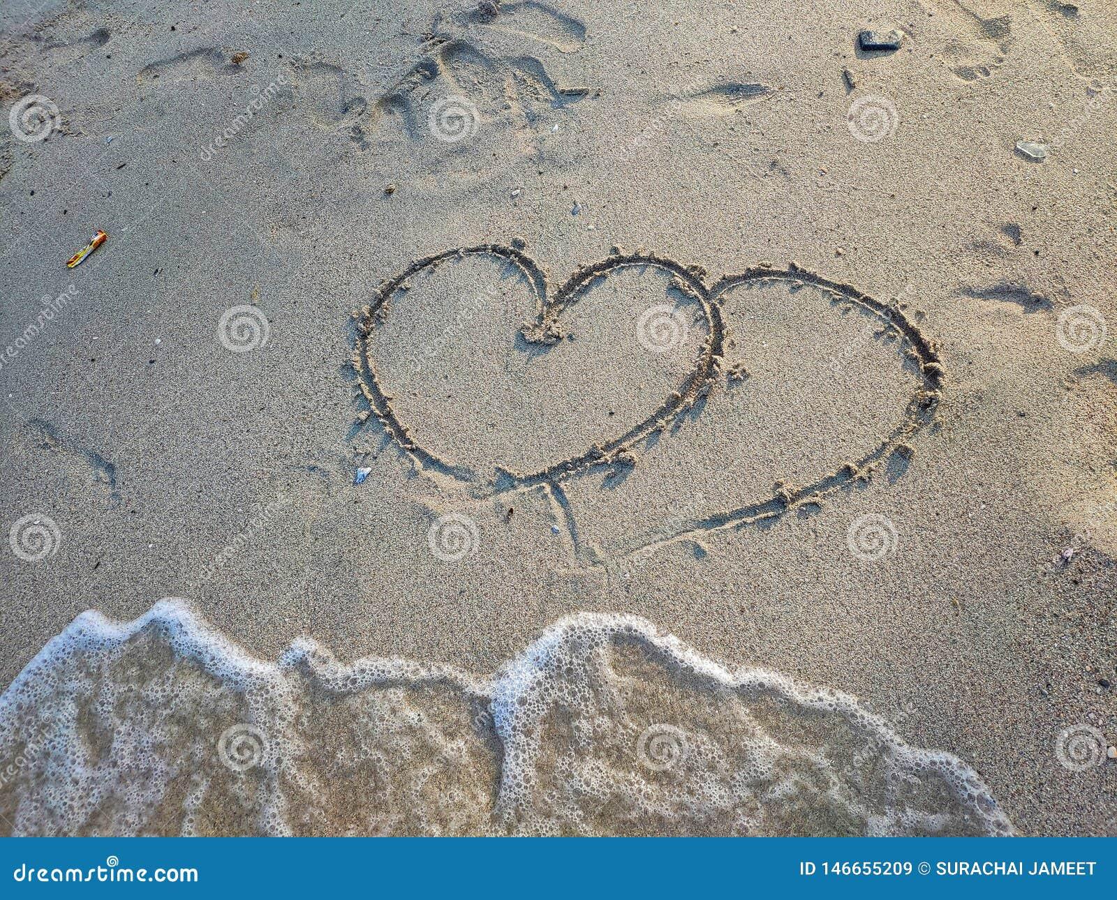 Na piasku, tam jest dwa serc rysowa? Pod s? b?bla fale przychodz? przestrze? troszk?, lata poj?cie poj?cia serce nad czerwieni r?