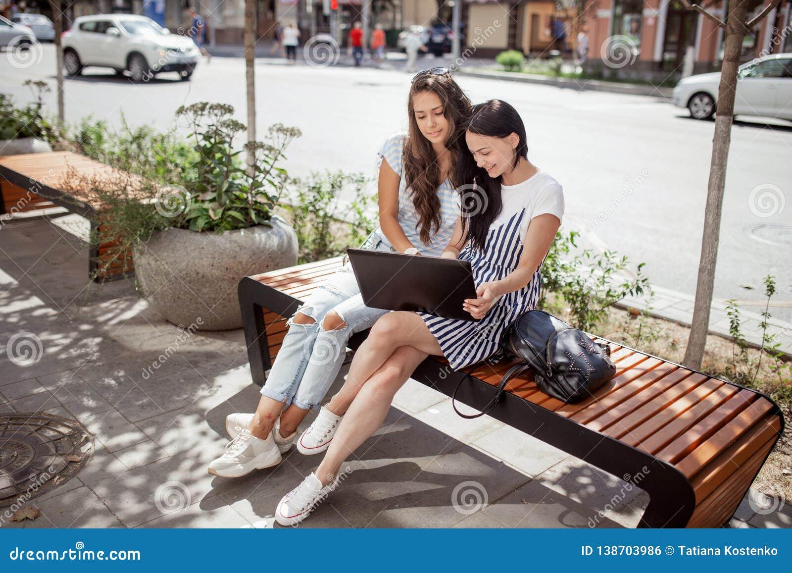 Na pogodnym popołudniu, dwa młodej ładnej damy z długim ciemnym włosy, jest ubranym przypadkowych slothes, siedzą na ławce obok e