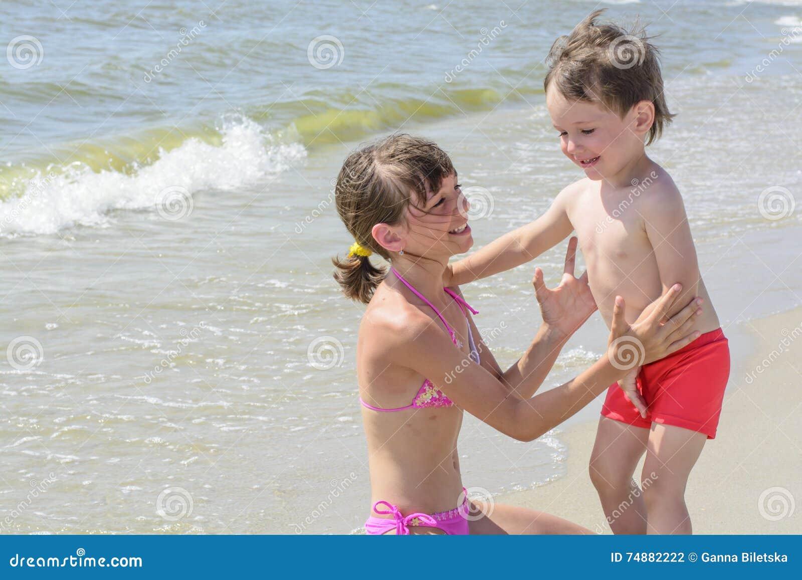 Na praia a irmã mais idosa quer abraçar um irmão do bebê, e contra o contexto do mar acena