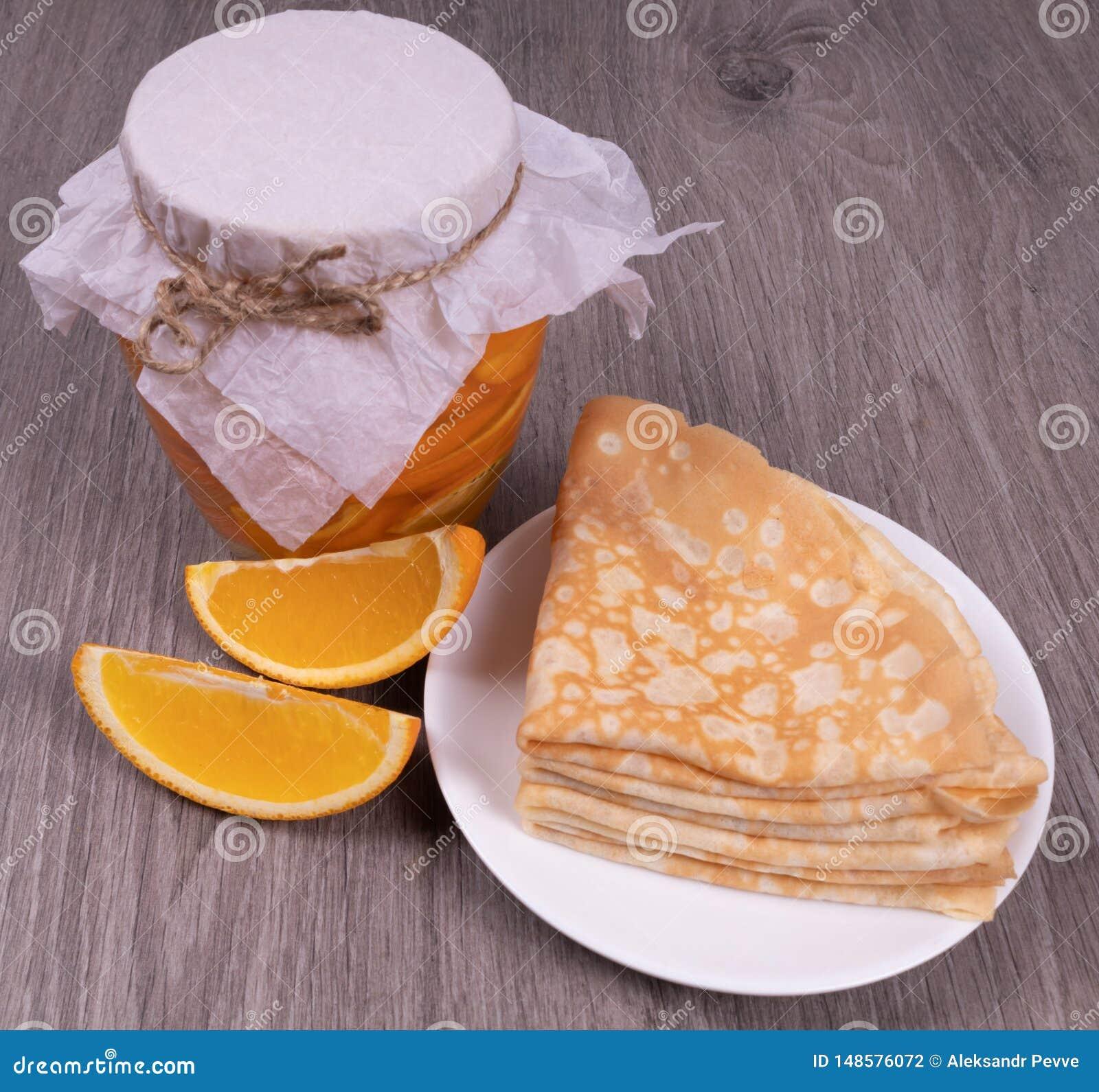Na textured drewnianym tle, słój pomarańczowy syrop obok go jest talerzem bliny i pokrojeni †‹â€ ‹pomarańcze plasterki