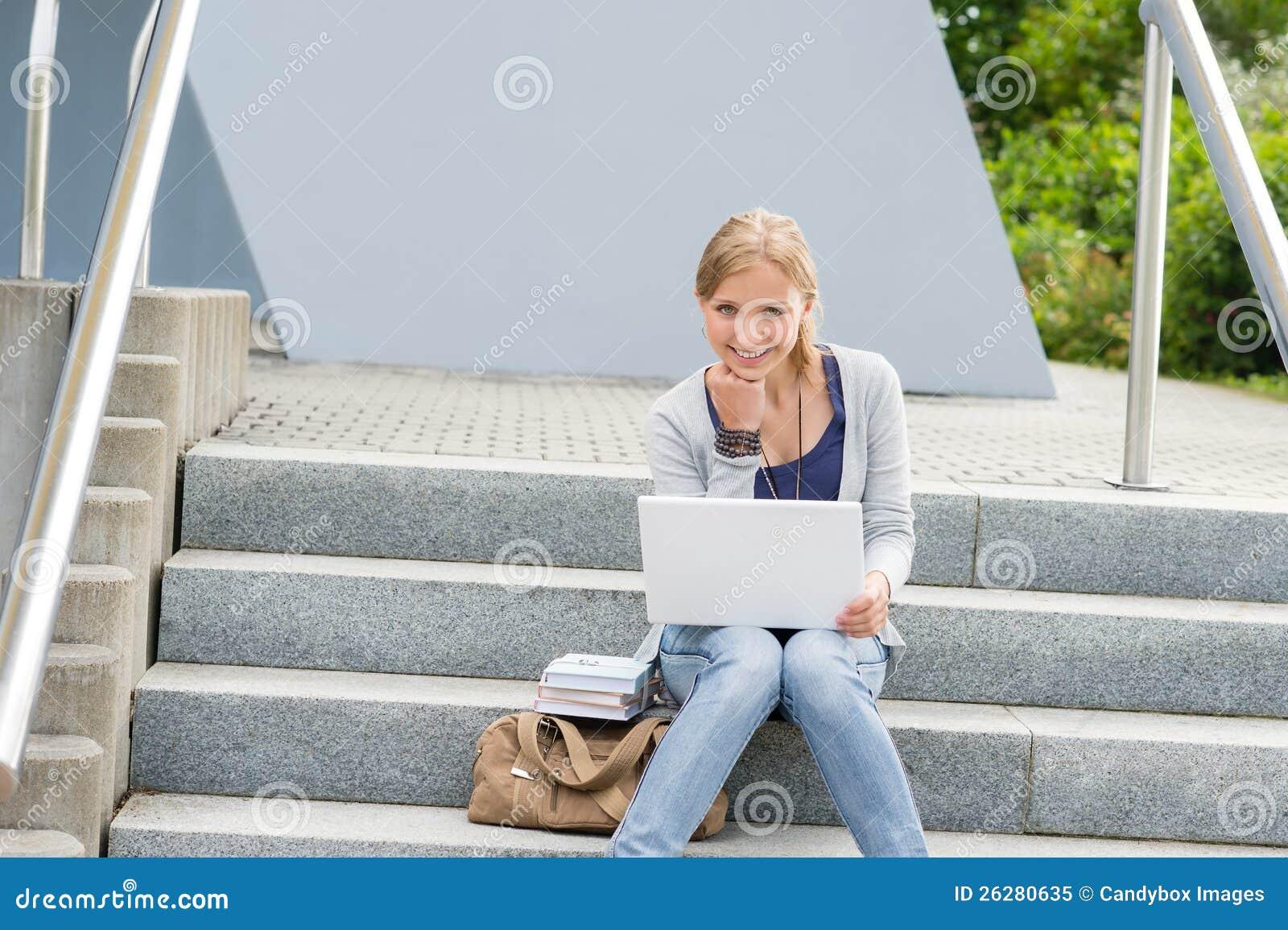 Na uniwersyteckich krokach kobiety młody studencki obsiadanie