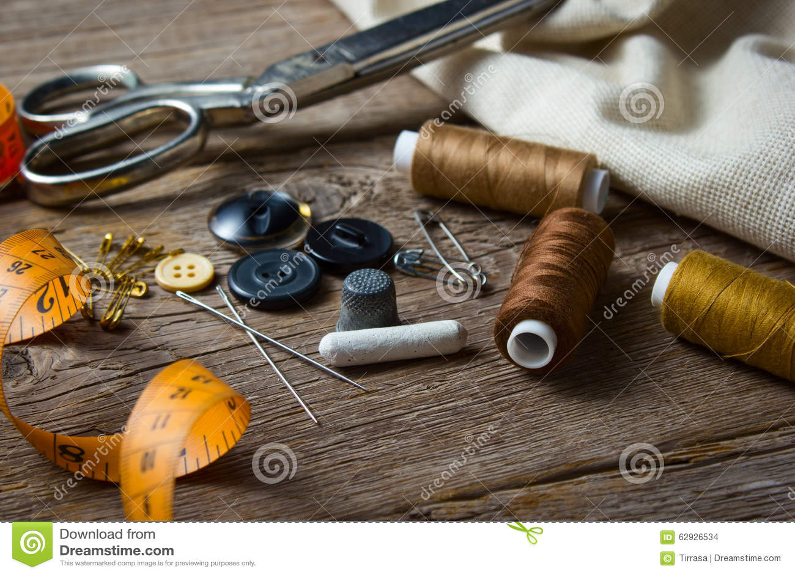 Naaiende toebehoren op houten lijst