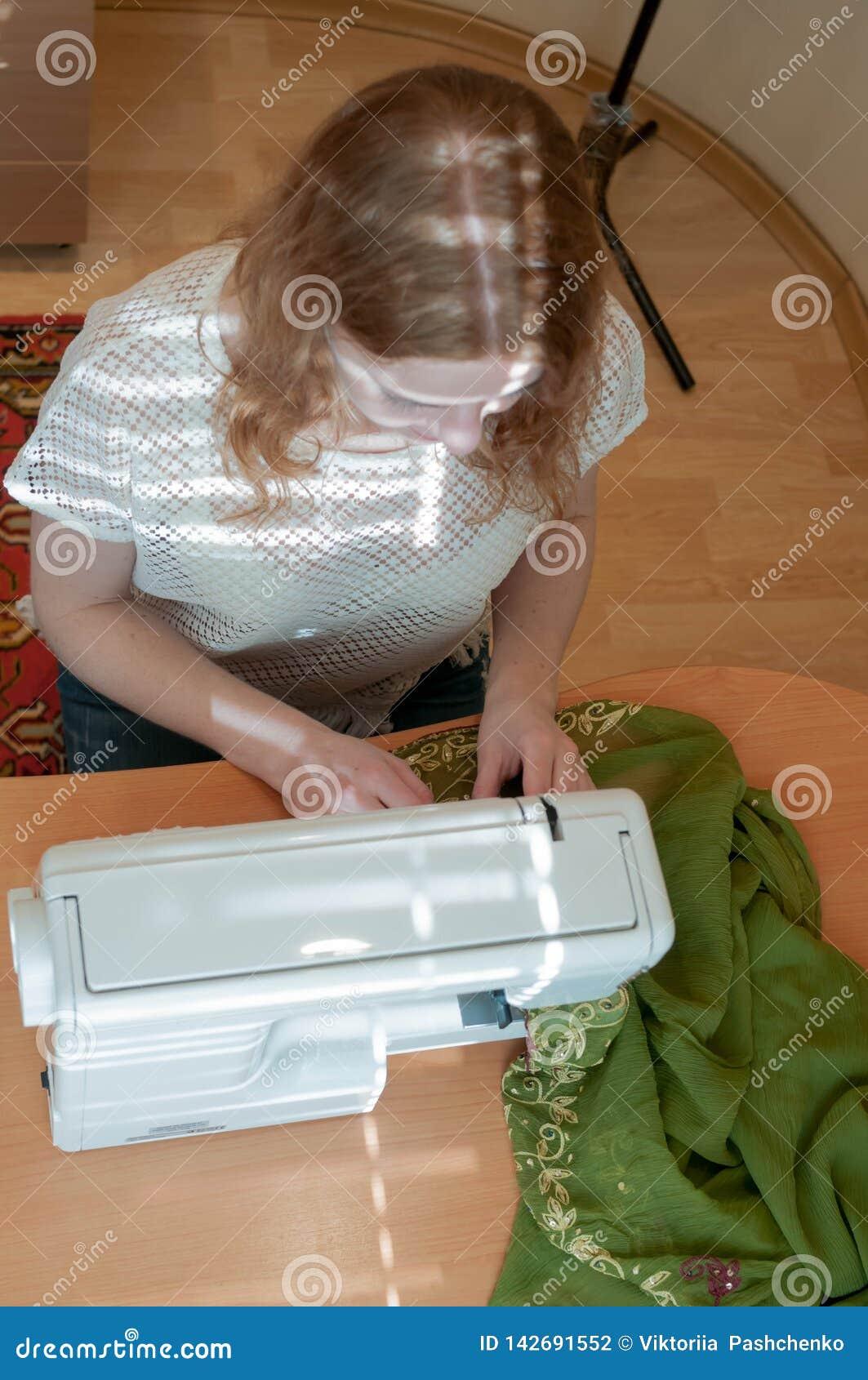 Naaisterszitting bij houten lijst met naaimachine, doek en het werken