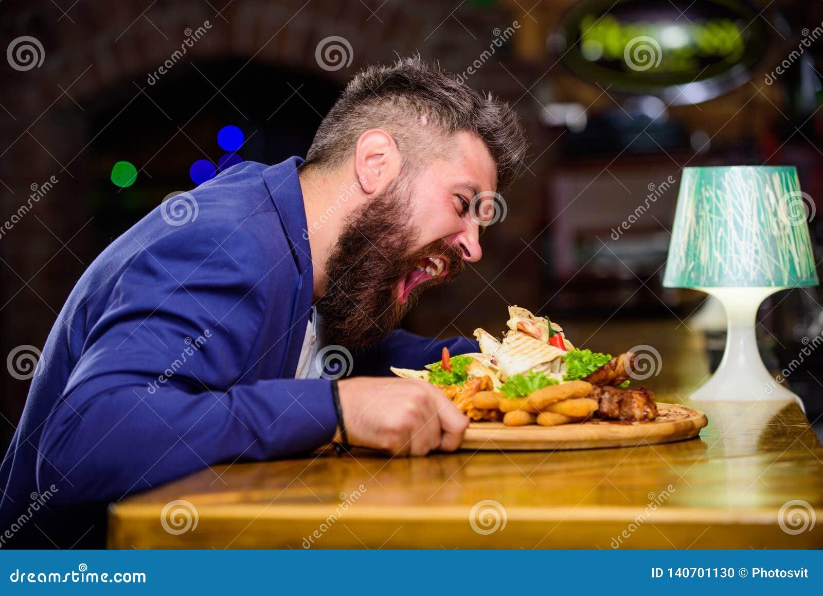 Nabranie posiłku pojęcie Modniś głodny je pub smażącego jedzenie Kierownika formalny kostium siedzi przy baru kontuarem Wyśmienic