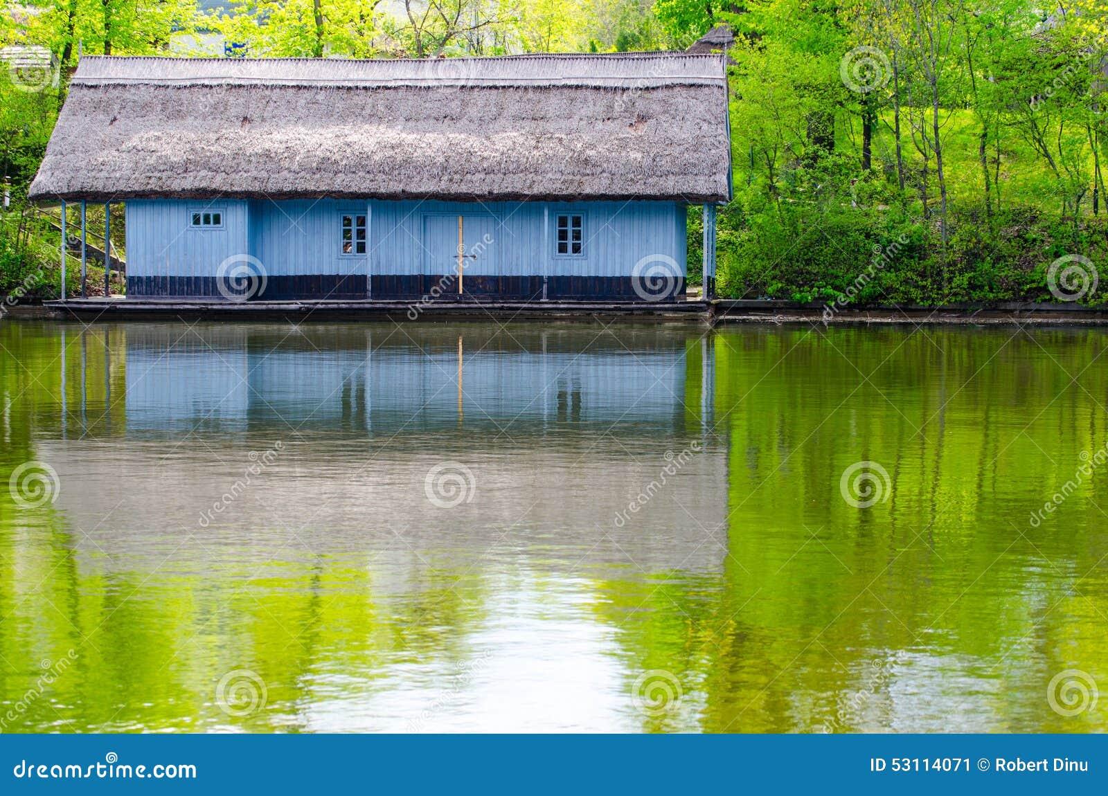 Nabrzeże drewniany dom z pokrywającym strzechą dachem Malujący w błękicie