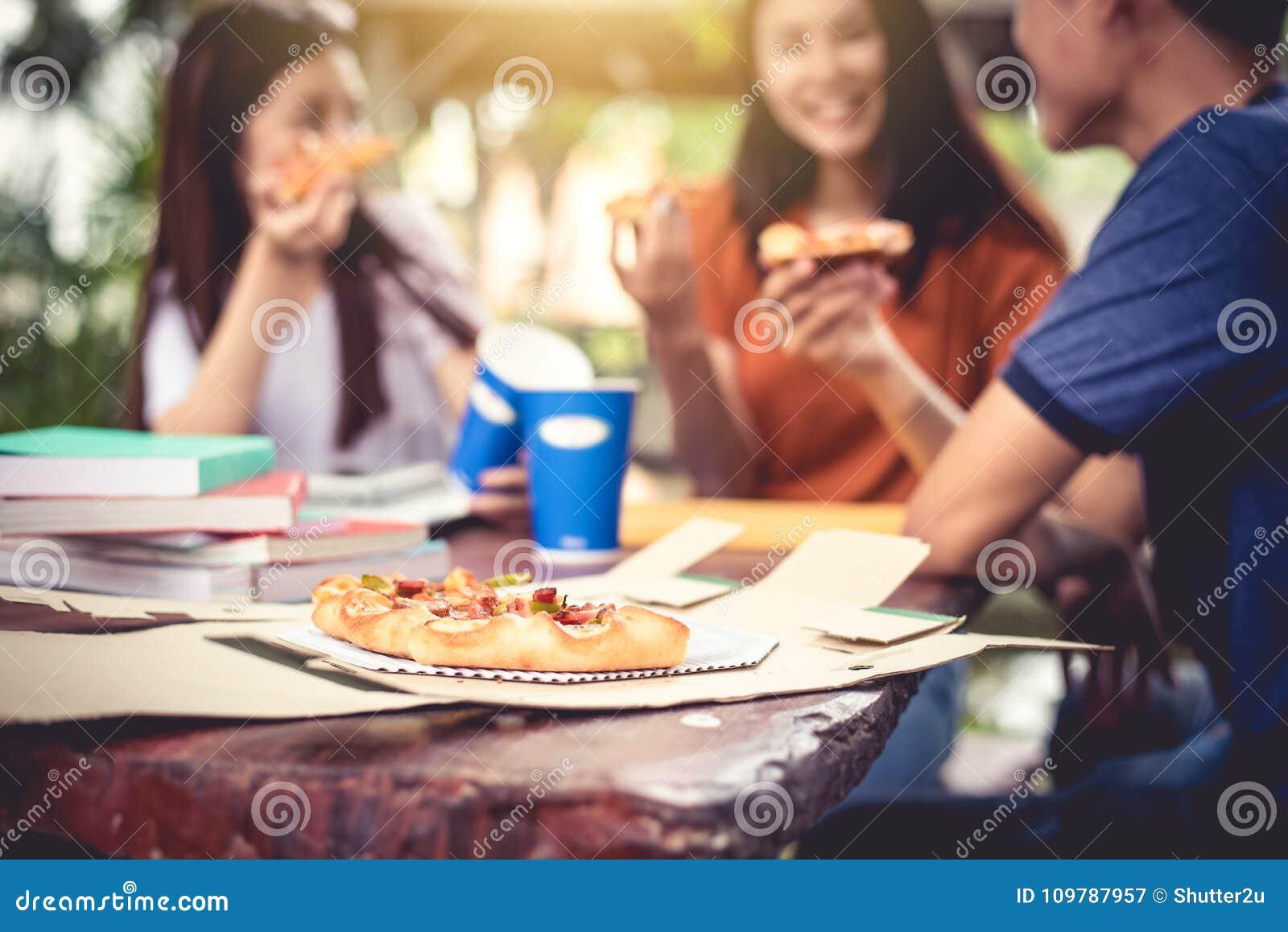 Nach der Unterrichtung drei asiatische, Leute genießen Pizza am Freien zu essen