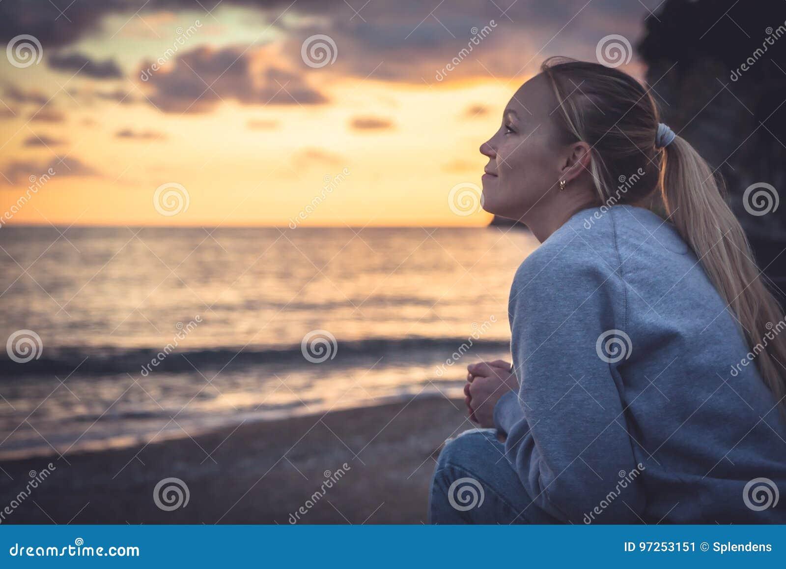Nachdenkliche einsame lächelnde Frau, die mit Hoffnung in Horizont während des Sonnenuntergangs Strand betrachtet