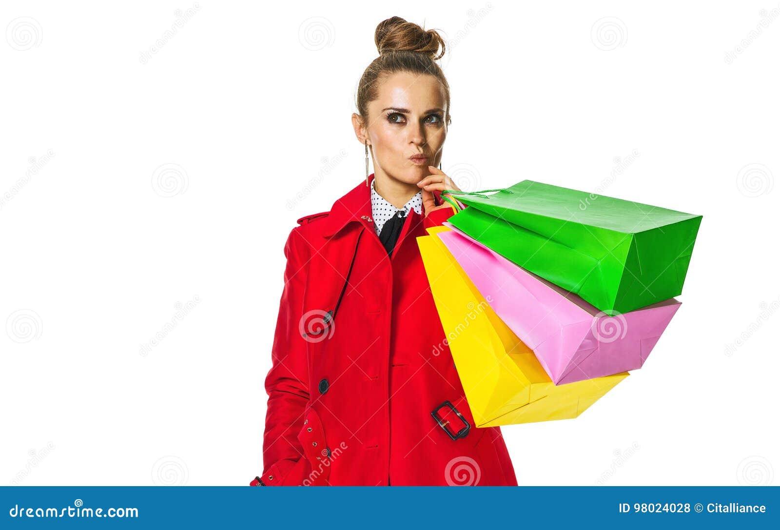 Nachdenkliche junge Frau im roten Mantel auf Weiß mit Einkaufstaschen