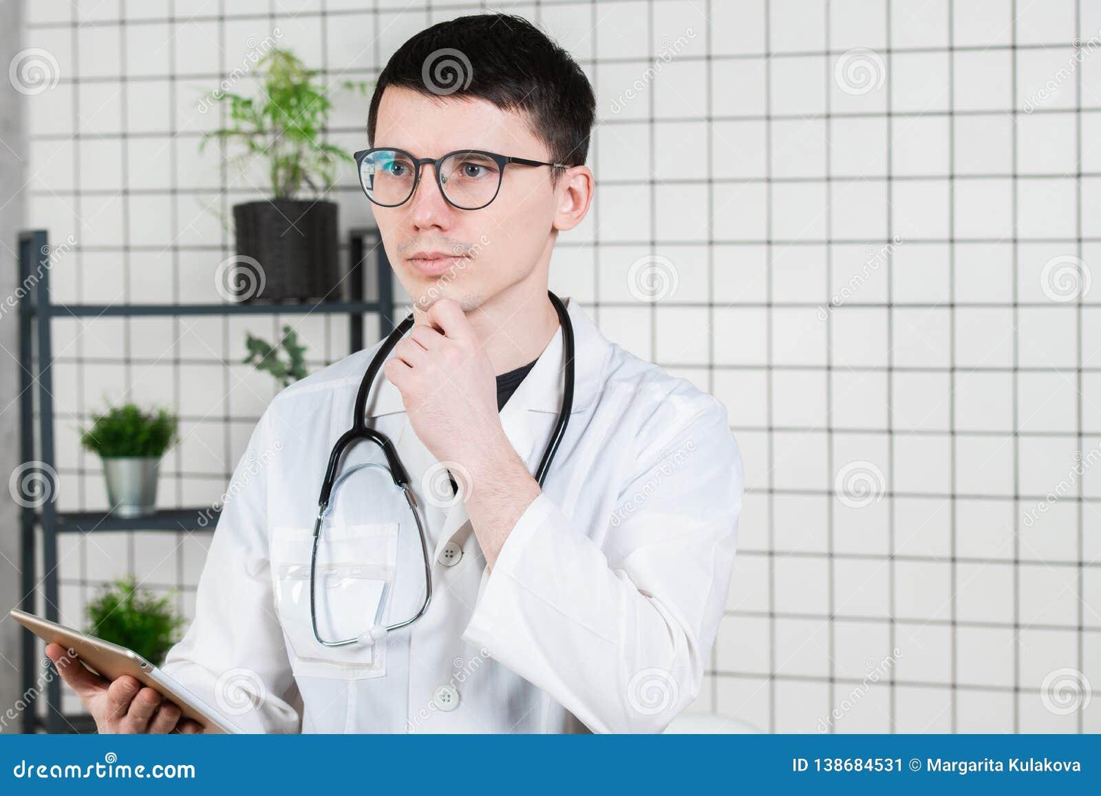 Nachdenklicher hübscher junger männlicher Doktor unter Verwendung des Tablet-Computers Technologien im Medizinkonzept