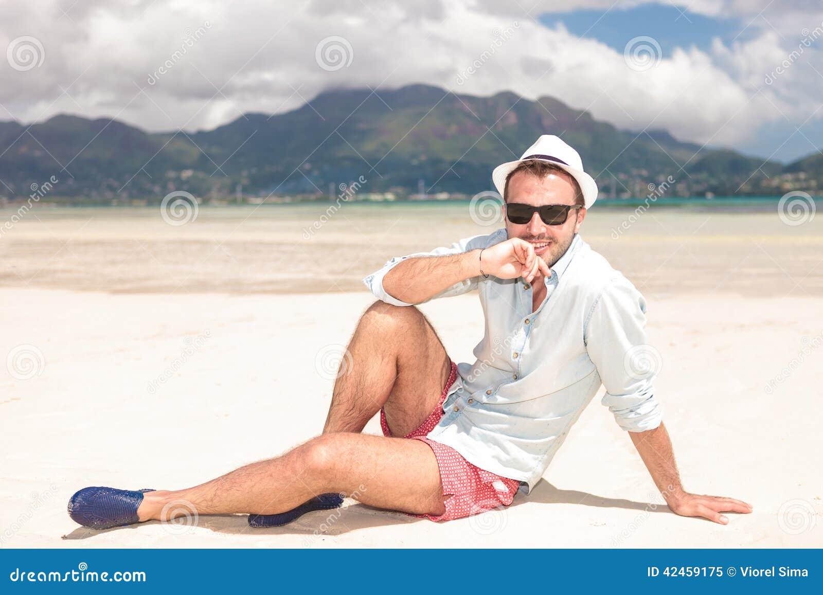 Nachdenklicher junger Mann, der auf dem Strand sitzt