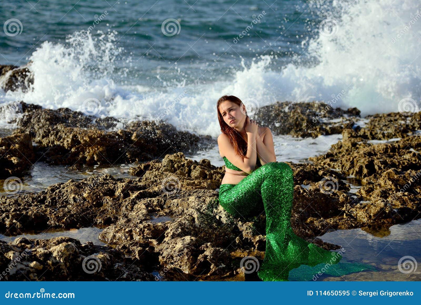 Nachdenkliches Mädchen in einer grünen Meerjungfrau, die Kostüm auf den Felsen auf der Küste auf dem Hintergrund des Wassers sitz